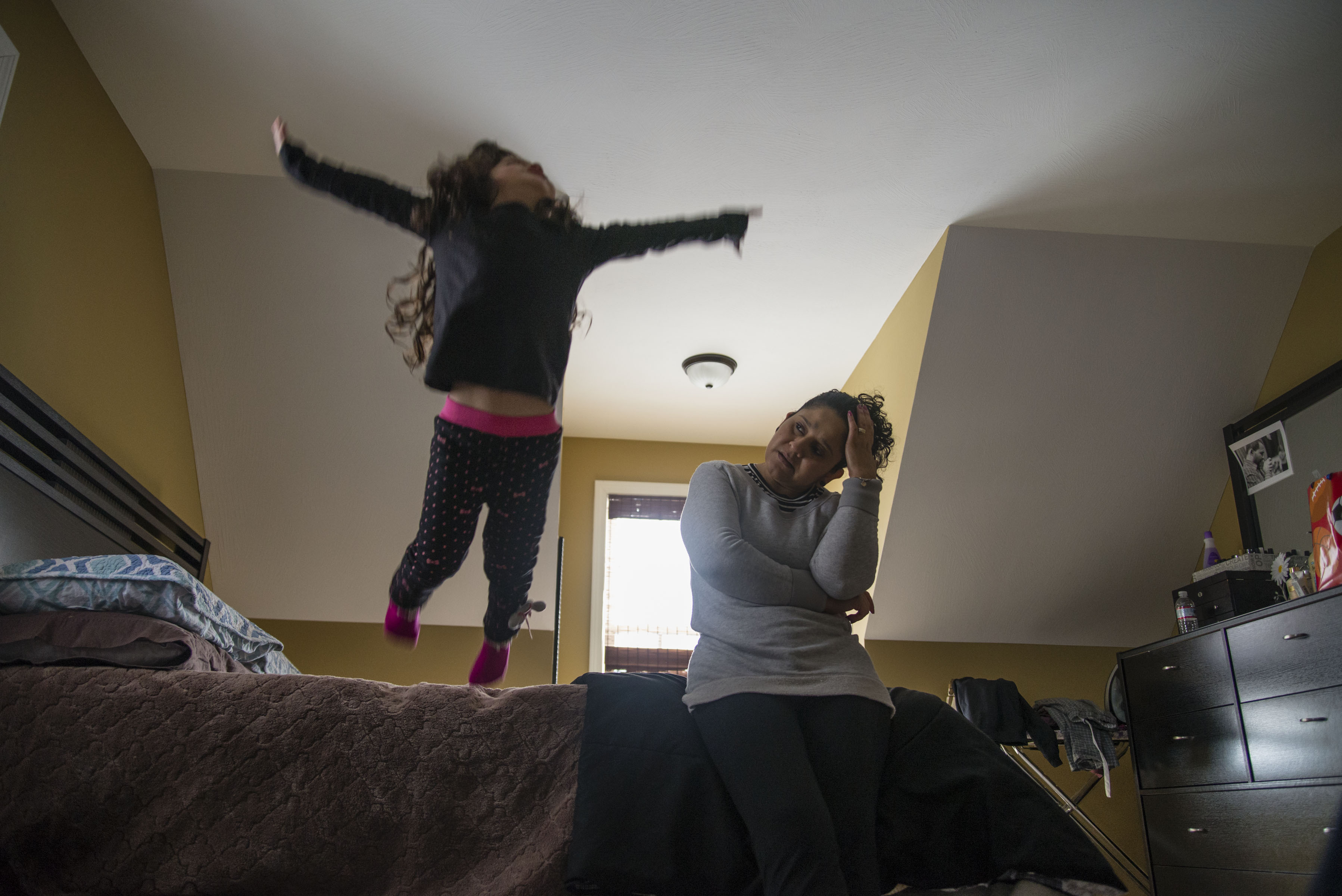 """In this photo, Rubi is jumping off the bed and yelling, """"Fly, fly away, Tia Iari!"""" My mother stopped working a couple years back when my stepfather's business really picked up. During that time, my niece, Rubi, was born. My mother would babysit Rubi while my sister worked. This September, Rubi began school. Now, my mother spends her time alone at home. I feel like my mother is depressed and I try to keep her happy, but I can't be there for her all the time – I want to also make my life. I want to shoot, I want to use my work to create change. I just want to get out there and share my work, particularly during these difficult times. (Photo by Iaritza Menjivar/GroundTruth)"""