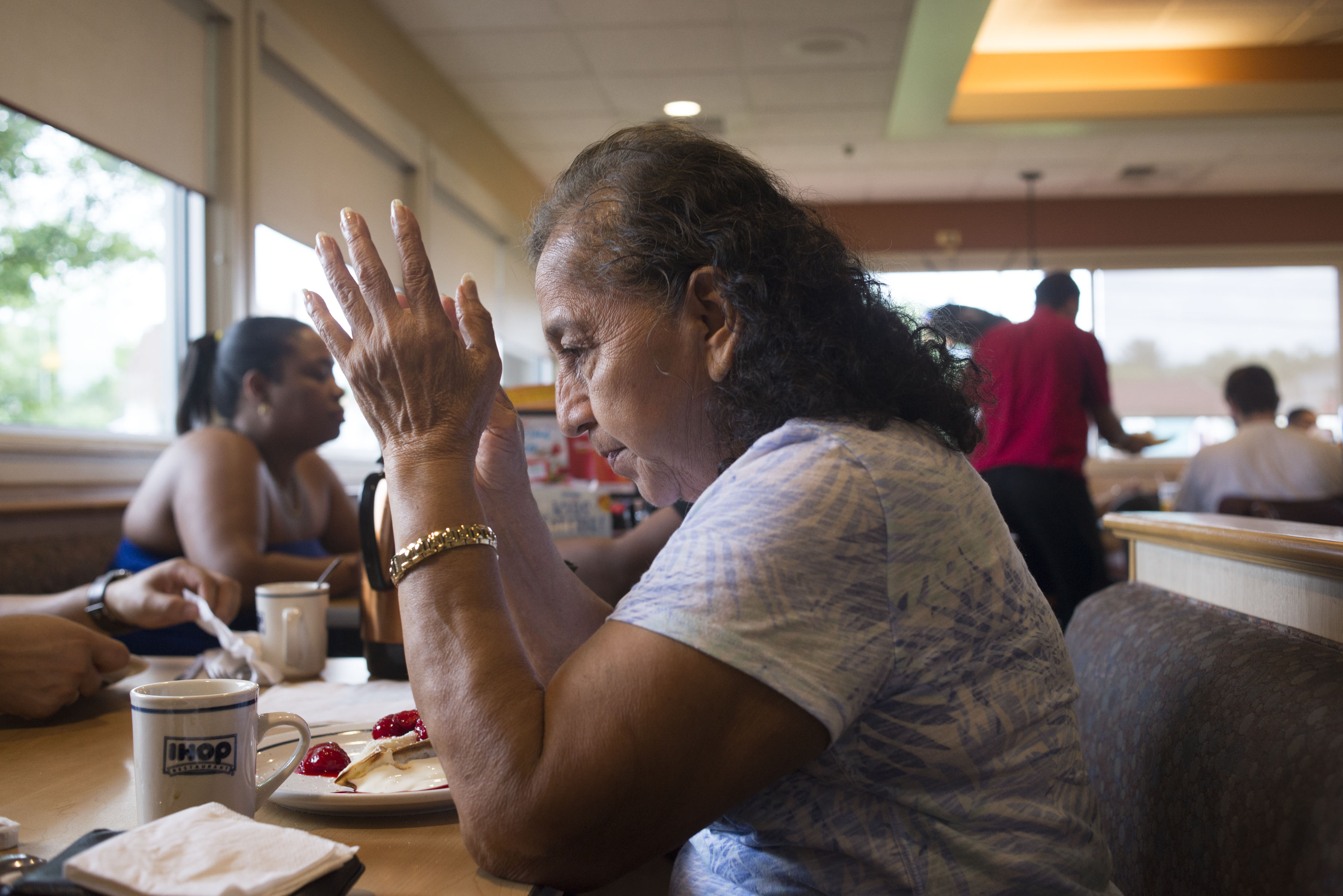 "My grandmother, Rosario Hernandez, prays before breakfast at IHop. ""Gracias, papa Dios por nuestros alimentos provelele al que no tiene,"" she said. In English: ""Thank you, God for our Food. Please provide for those who do not have."" (Photo by Iaritza Menjivar/GroundTruth)"