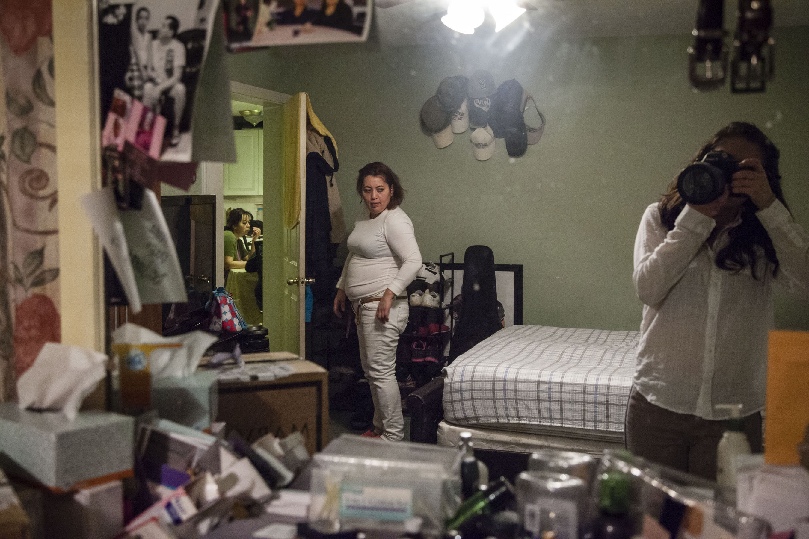 """My aunt, Maritza, stands in her home after a 12-hour shift at the factory. She is the first of our family to immigrate to the United States. """"If I stayed, I would've probably had five kids conforming to the typical Salvadoran lifestyle. You don't progress over there. I own my car now and, one, day I will have my home."""" (Photo by Iaritza Menjivar/GroundTruth)"""