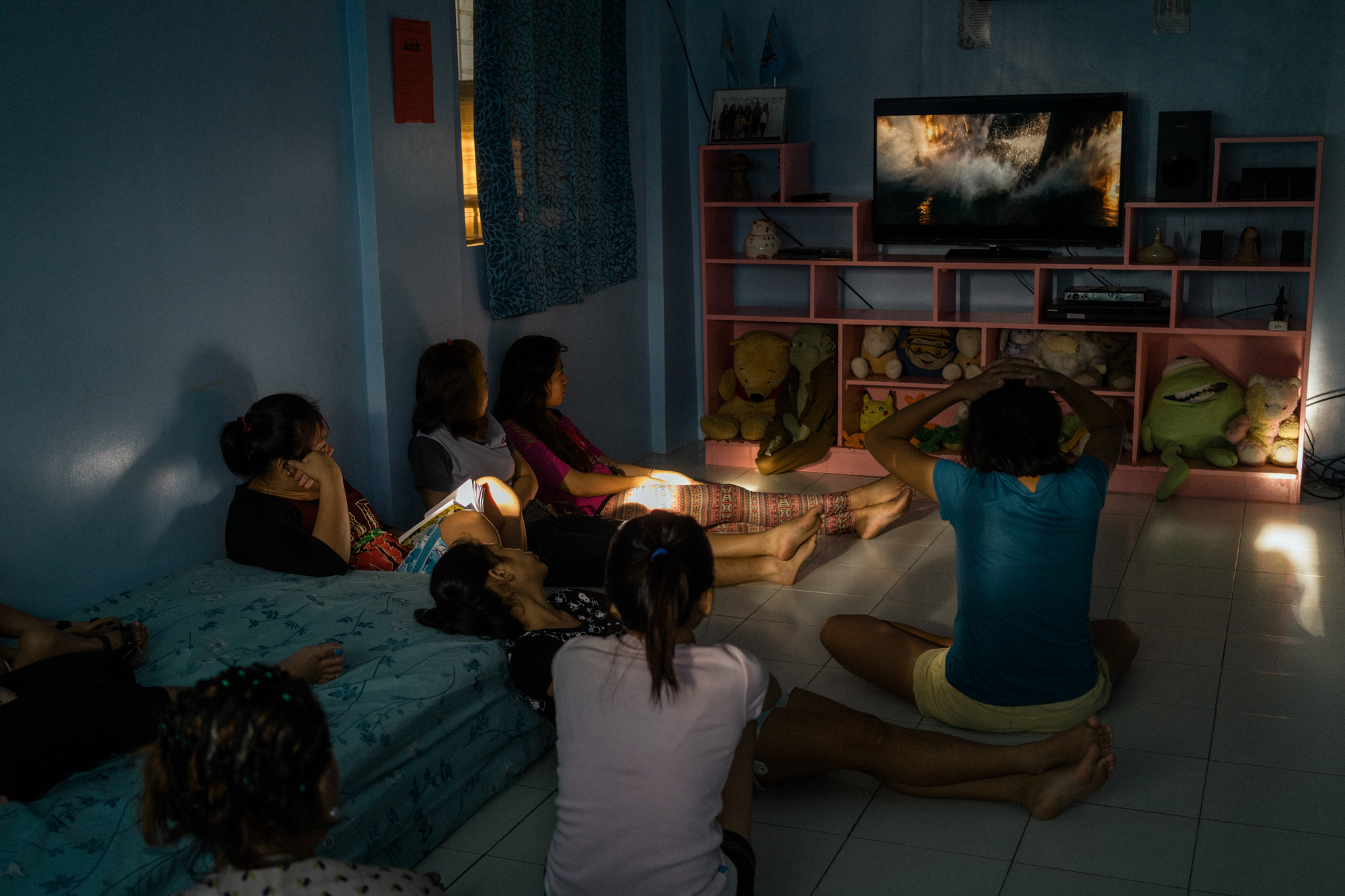 Girls watch television at a halfway house for victims of sex trafficking. Here, girls who are rescued get counseling, shelter, legal assistance, and, for some, education. (Photo by Hannah Reyes Morales/GroundTruth)