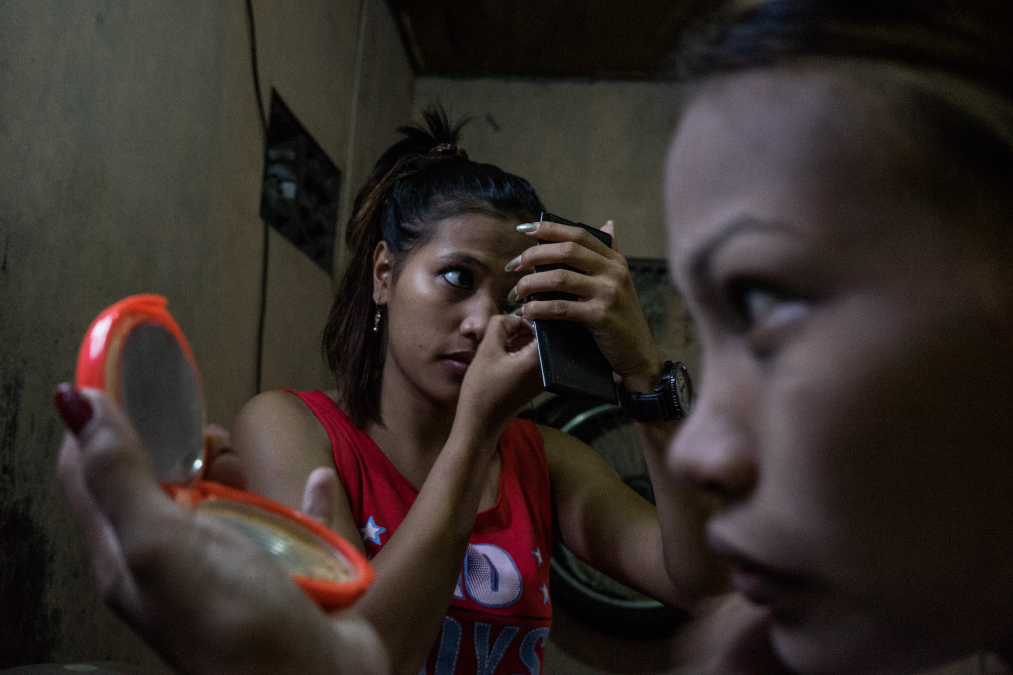 Sisters Gemma and Jojo do their makeup before a night of work in Angeles City, notorious for its sex tourism. (Photo by Hannah Reyes Morales/GroundTruth)