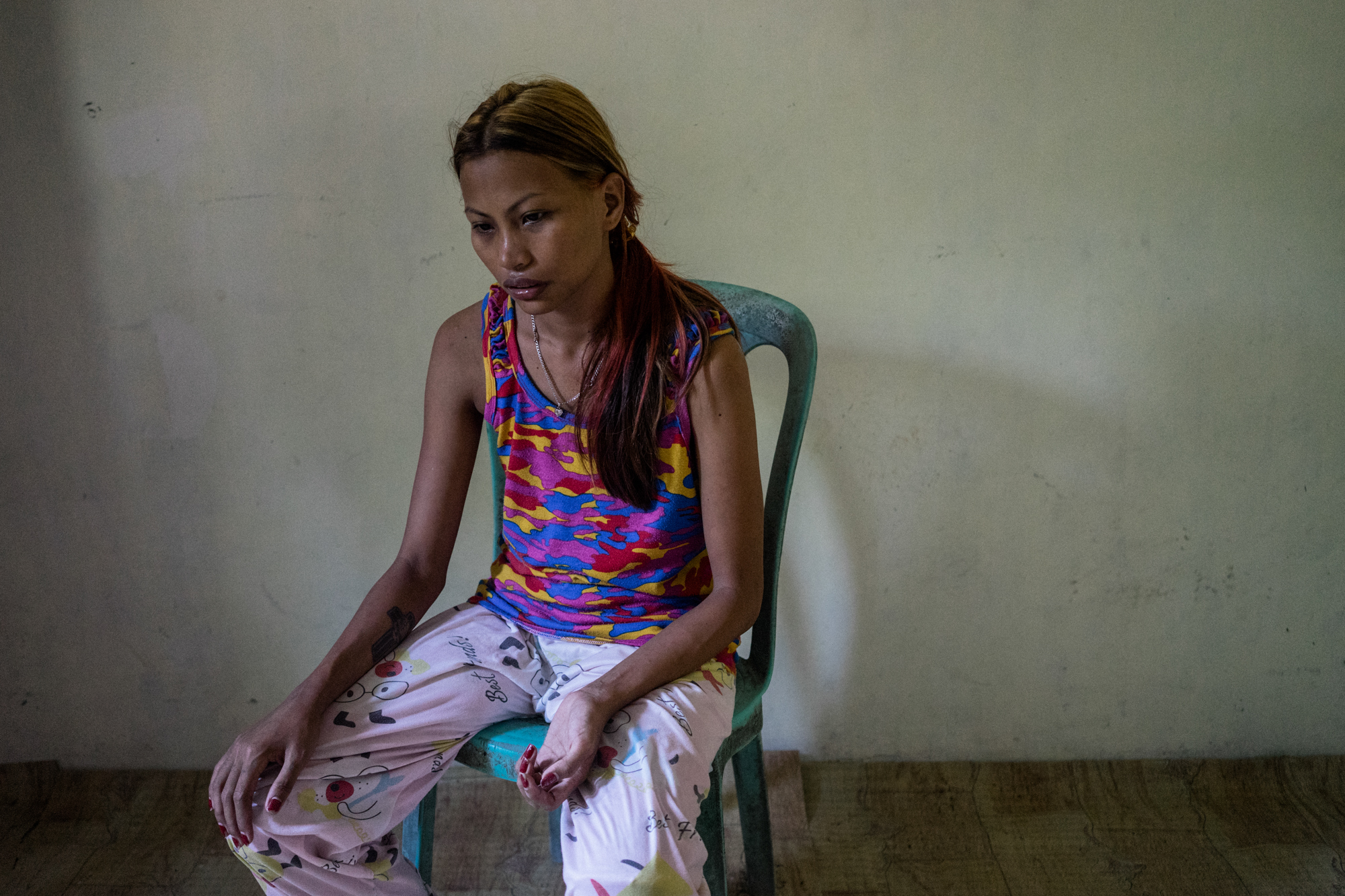 Jojo, who became a sex worker after a typhoon significantly damaged her home, sits in her house in Angeles City, notorious for its sex tourism and red light district. (Photo by Hannah Reyes Morales/GroundTruth)