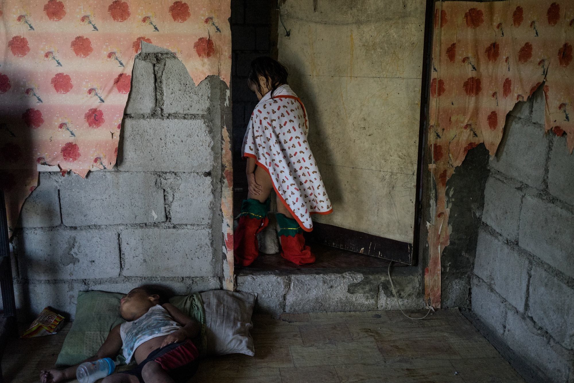 """Jojo's daughter stands in a doorway. Jojo says she dreams that her daughter be a lawyer, so that her """"whoring could at least have borne some fruit."""" (Photo by Hannah Reyes Morales/GroundTruth)"""
