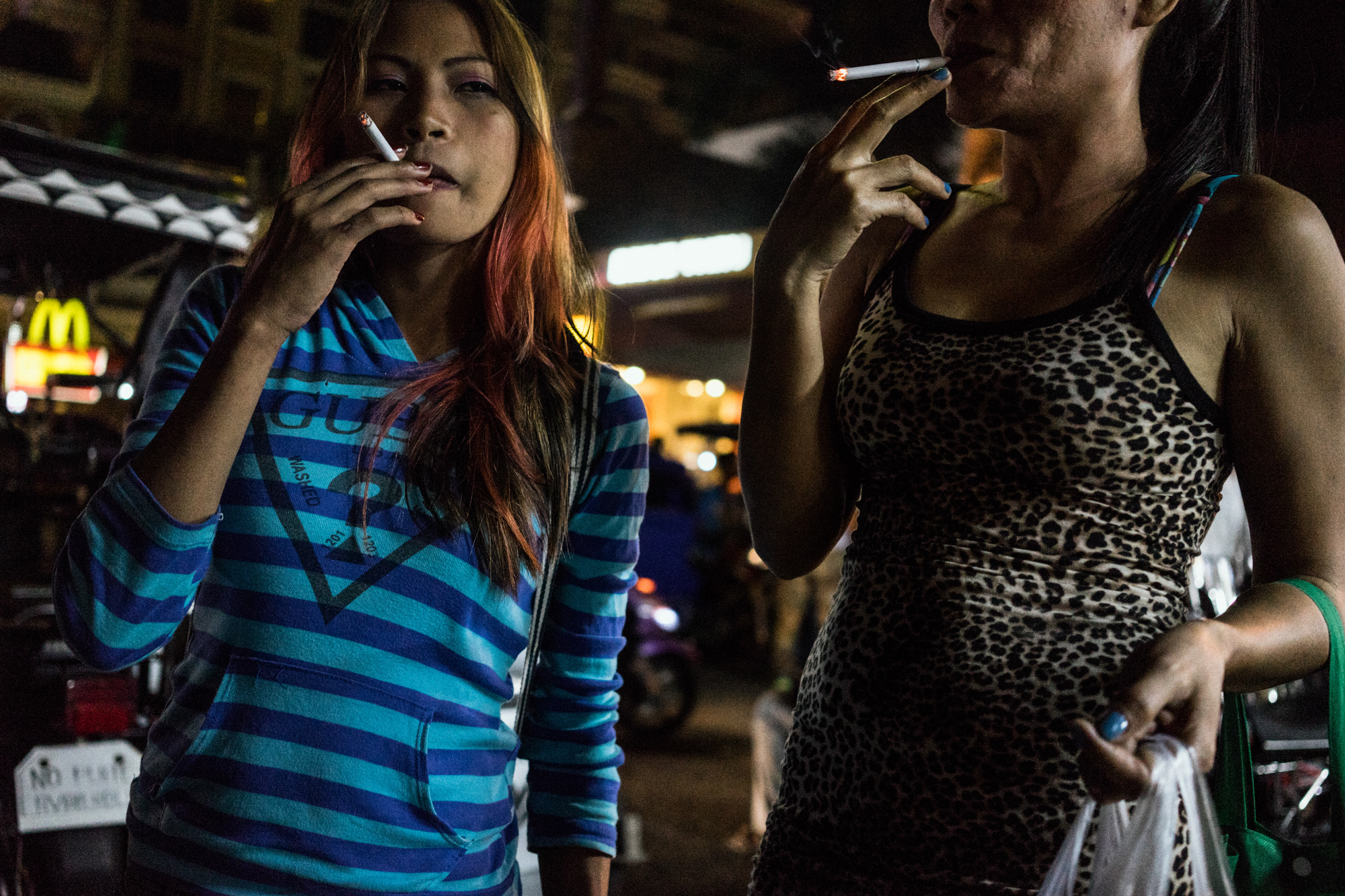 Jojo and Rose smoke cigarettes after a night at work in one of the bars in Angeles City. (Photo by Hannah Reyes Morales/GroundTruth)