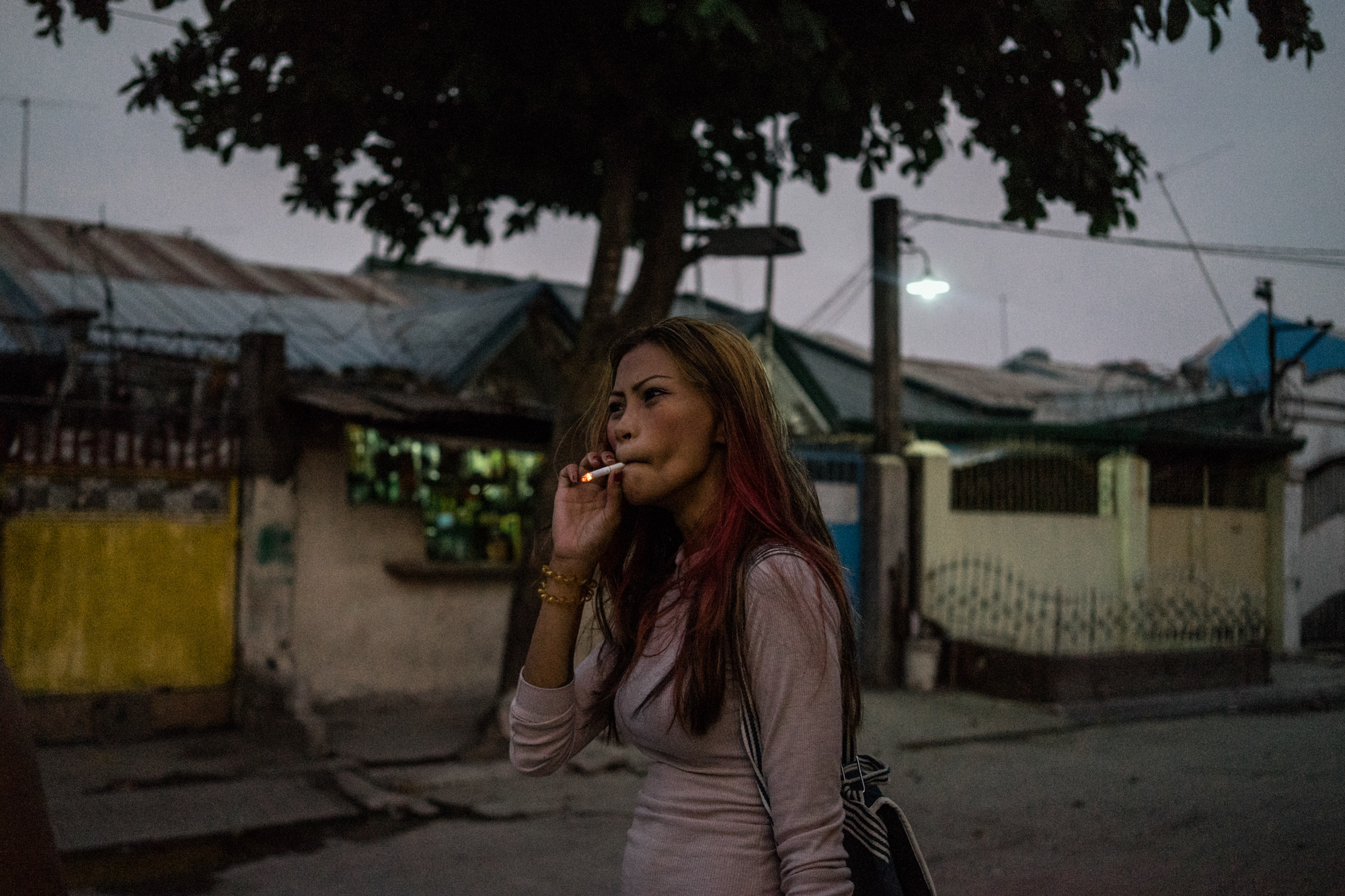 Jojo smokes while walking to work. (Photo by Hannah Reyes Morales/GroundTruth)