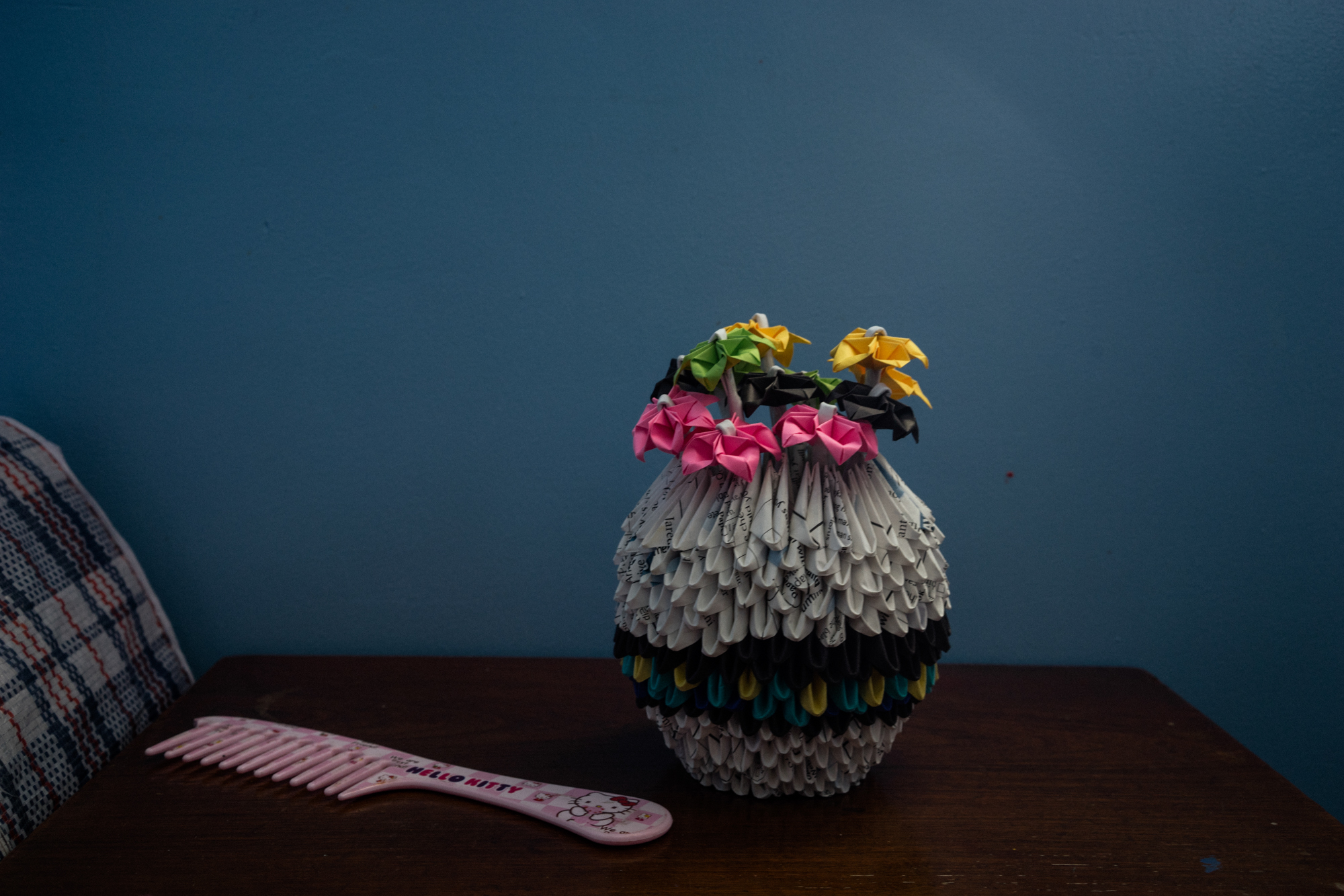 A paper vase of flowers and a comb sit on a table in a Philippine halfway house for victims of sex trafficking. (Photo by Hannah Reyes Morales/GroundTruth)
