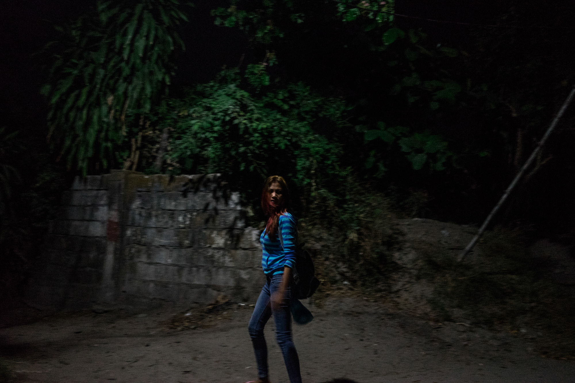 Jojo walks home after a night at work in one of the bars in Angeles City. Before typhoon Haiyan, she was trying to quit working in the sex industry and settle back to Leyte, but when the storm came, she had to go back. (Photo by Hannah Reyes Morales/GroundTruth)