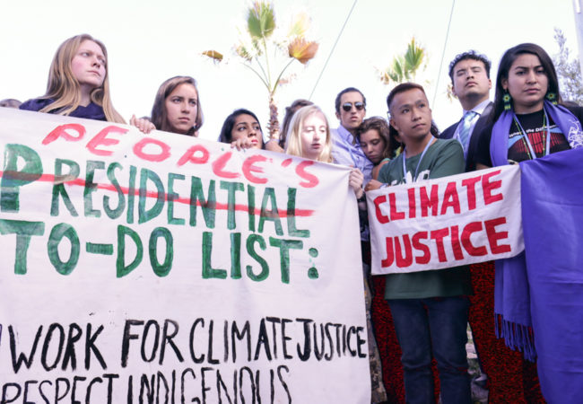 Worried climate justice advocates hold up a to-do list to address climate change and its many effects in lieu of Donald Trump's upcoming U.S. presidency. (Photo by Justine Calma/GroundTruth)