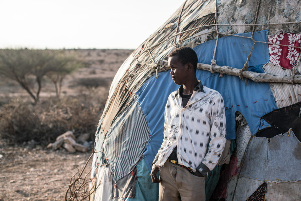 A boy stands outside his family's home at dawn in Gebiley region, Somalia, amidst a severe drought that swept across northwestern Somalia. (Photo by Nichole Sobecki/GroundTruth)