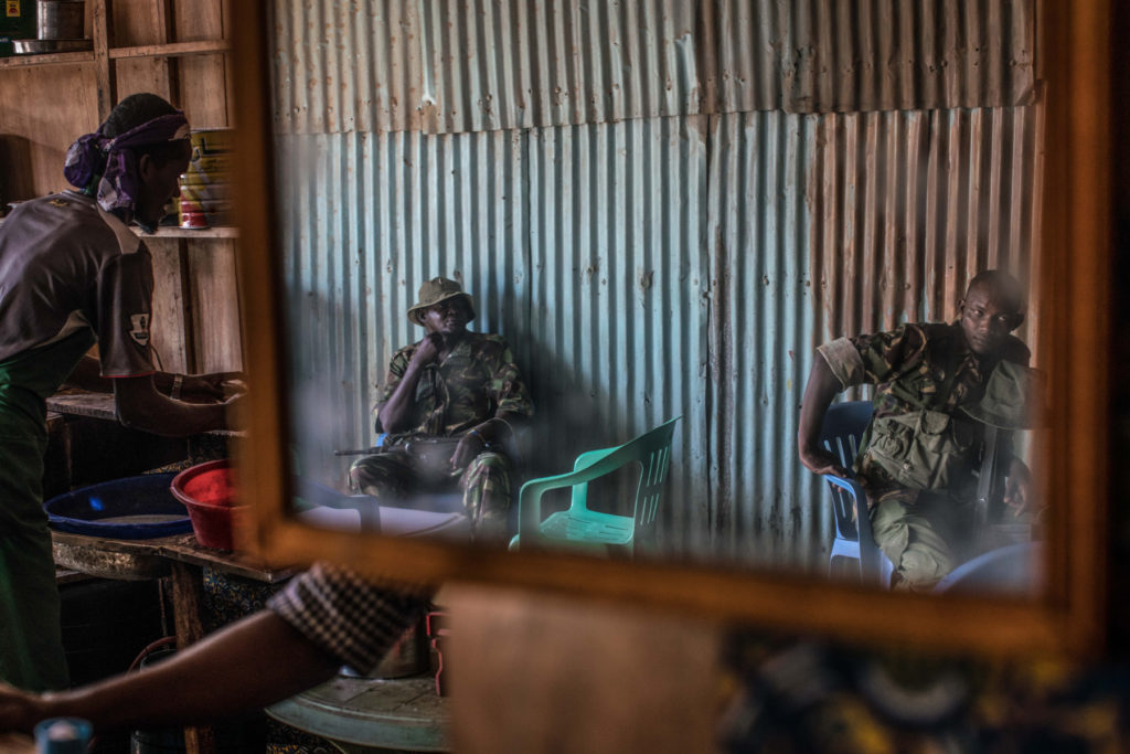 Armed police sit in a cafe in one of Dadaab's many markets. Rights group have reported strong evidence showing that Kenyan police have carried out extrajudicial killings and enforced disappearances in Dadaab and elsewhere in the country. (Photo by Nichole Sobecki/GroundTruth)