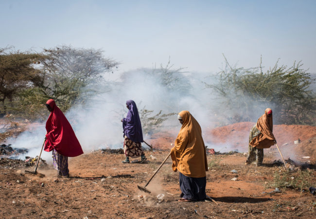 Women burn trash on the roadside in Dadaab refugee camp. In 2011, a severe drought pushed tens of thousands of Somalis from their homes, swelling the camp's population. Host to more than a third of a million people, Dadaab is the world's largest refugee camp, but it's now in danger of being shut down. (Nichole Sobecki/GroundTruth)