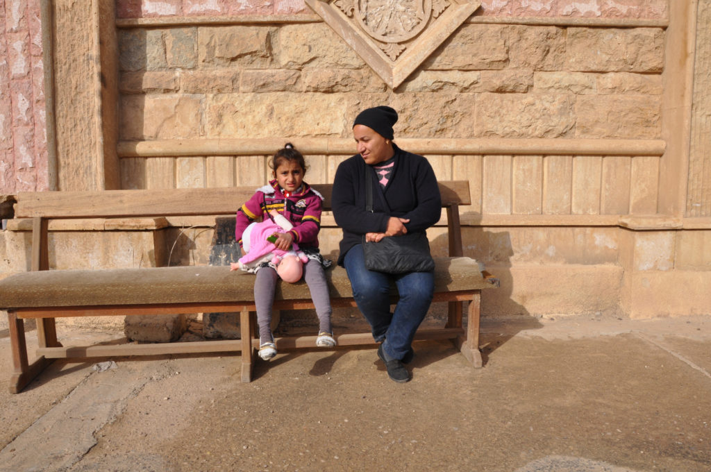 Saha and her daughter Mariam sit outside of their old church, now destroyed. (Photo by Lauren Bohn/GroundTruth)