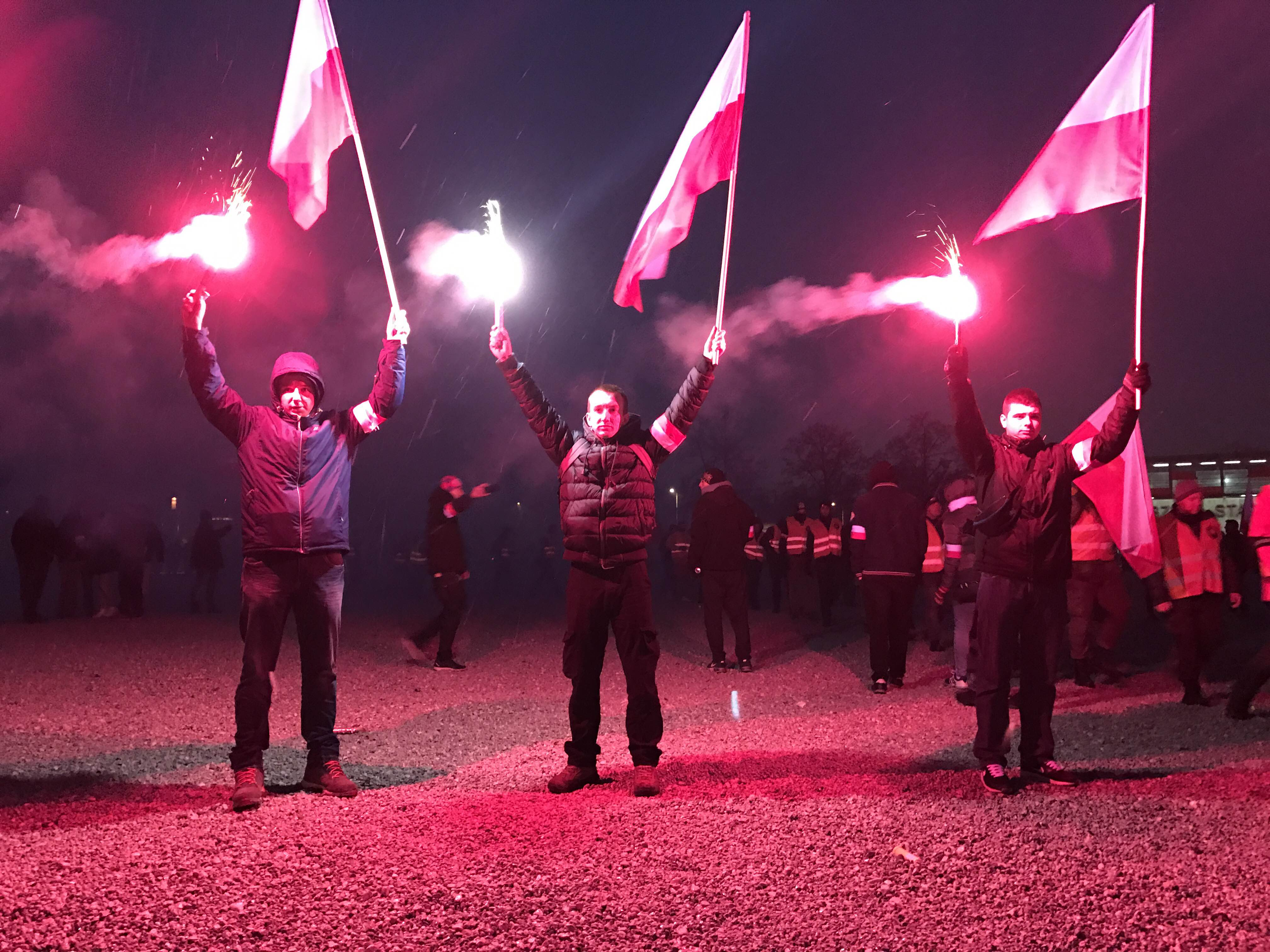 Young Poles stand silently while holding red flares and Polish flags and listen to speeches outside the National Stadium in Warsaw (Photo by Karolina Chorvath/GroundTruth)