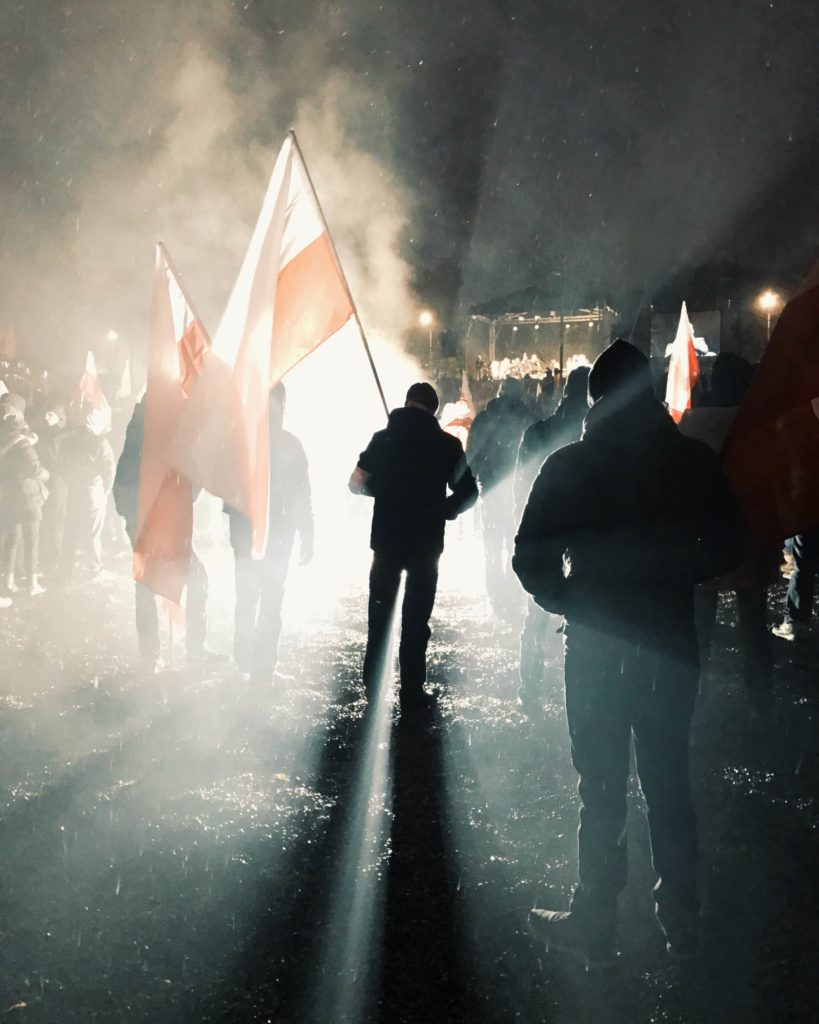 A Polish nationalist demonstrator stands outside of National Stadium in Warsaw at Independence Day rallies in 2016. (Photo by Karolina Chorvath/GroundTruth)