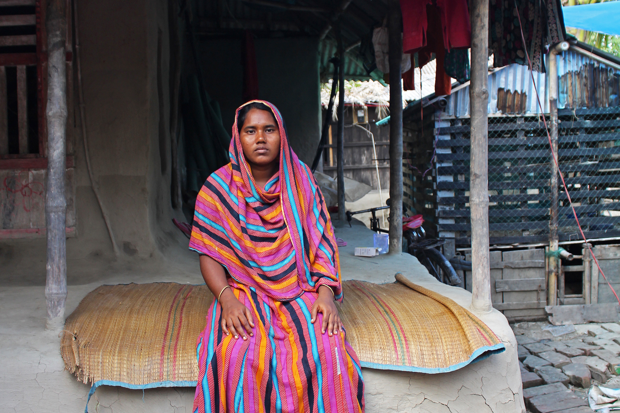 Romesa Khatun sits on her porch, an extension of the raised mud platform on which her house is built. Her home, like most others in the village, was completely destroyed during Aila, a devastating cyclone in 2009. (Photo by Neha Thirani Bagri/GroundTruth)