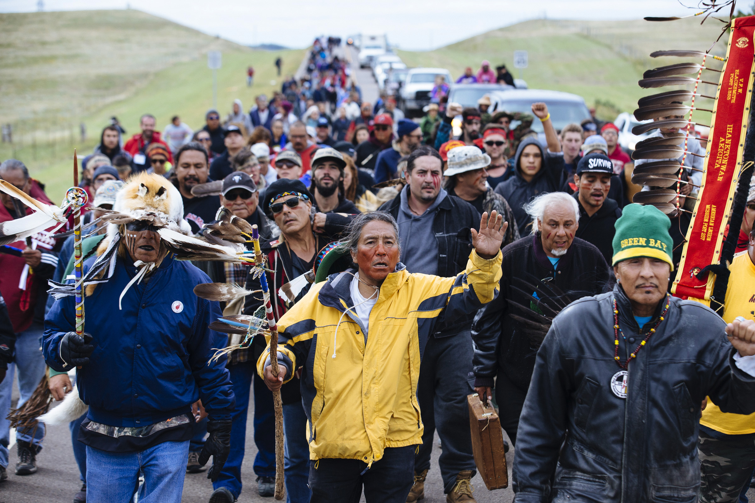 Stanley Perry (center), 53, from the Navajo Nation at the front of a protest march along Highway 1806 with over 700 water protectors on Friday, Sept. 9, 2016. The march covered the 2 miles between the Oceti Sakowin Camp and a sacred burial site, which is slated to be destroyed by the Dakota Access Pipeline. (Photo by Angus Mordant/Groundtruth)