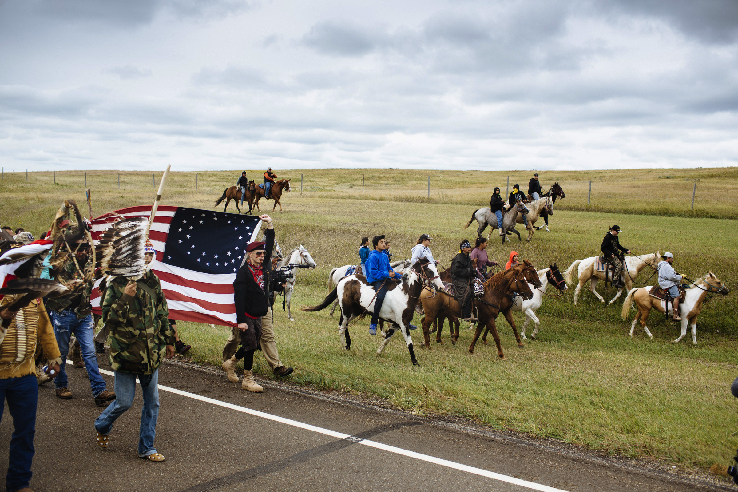 Horses lead a march of 700 protestors North along Highway 1806 in Morton County, North Dakota on Friday, Sept. 9, 2016. The march covered the 2 miles between the Oceti Sakowin Camp and a sacred burial site which is slated to be destroyed by the Dakota Access Pipeline. (Photo by Angus Mordant/Groundtruth)