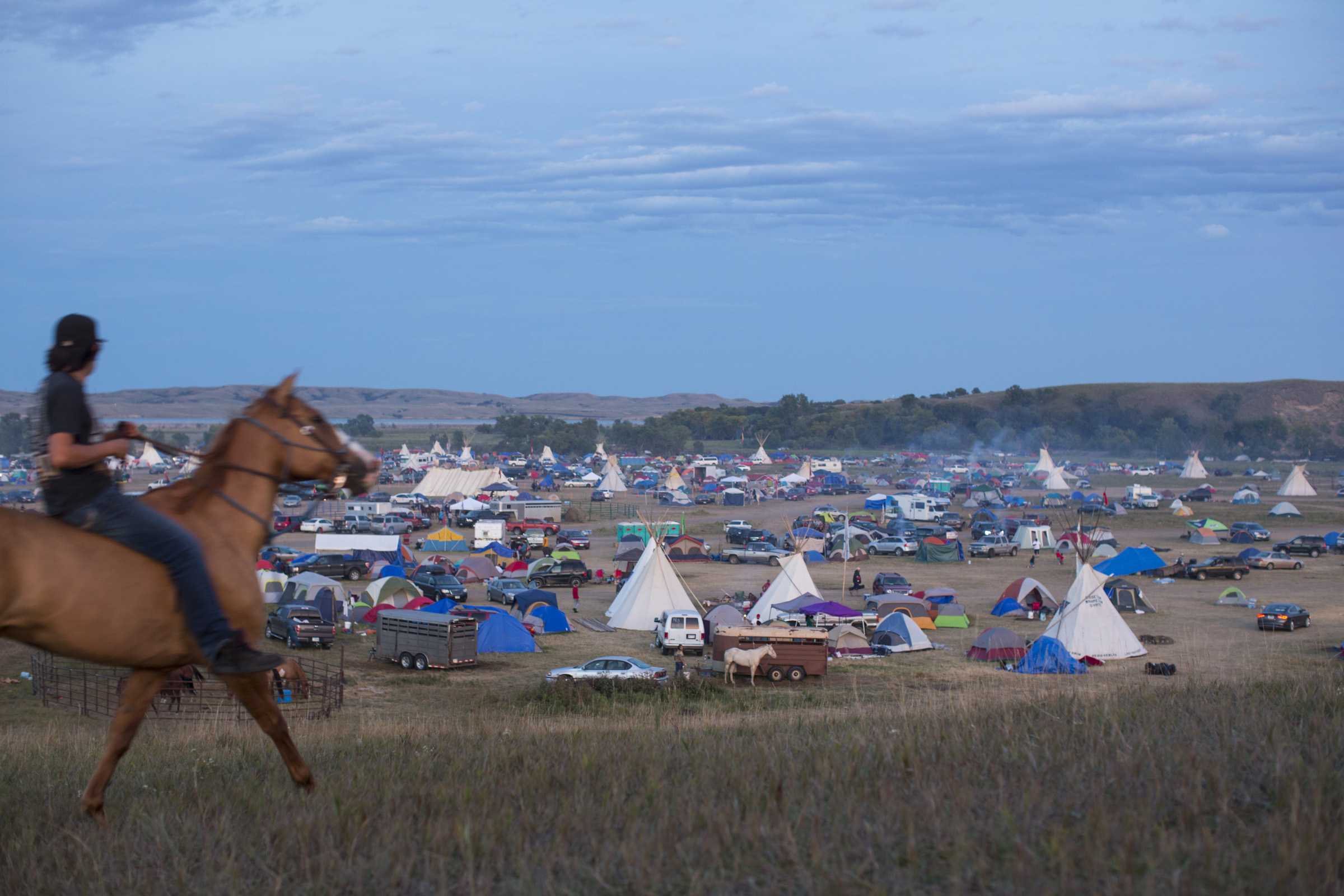 A man rides his horse up a hill overlooking the Oceti Sakowin Camp on Sunday, Sept. 11, 2016. (Photo by Angus Mordant/Groundtruth)