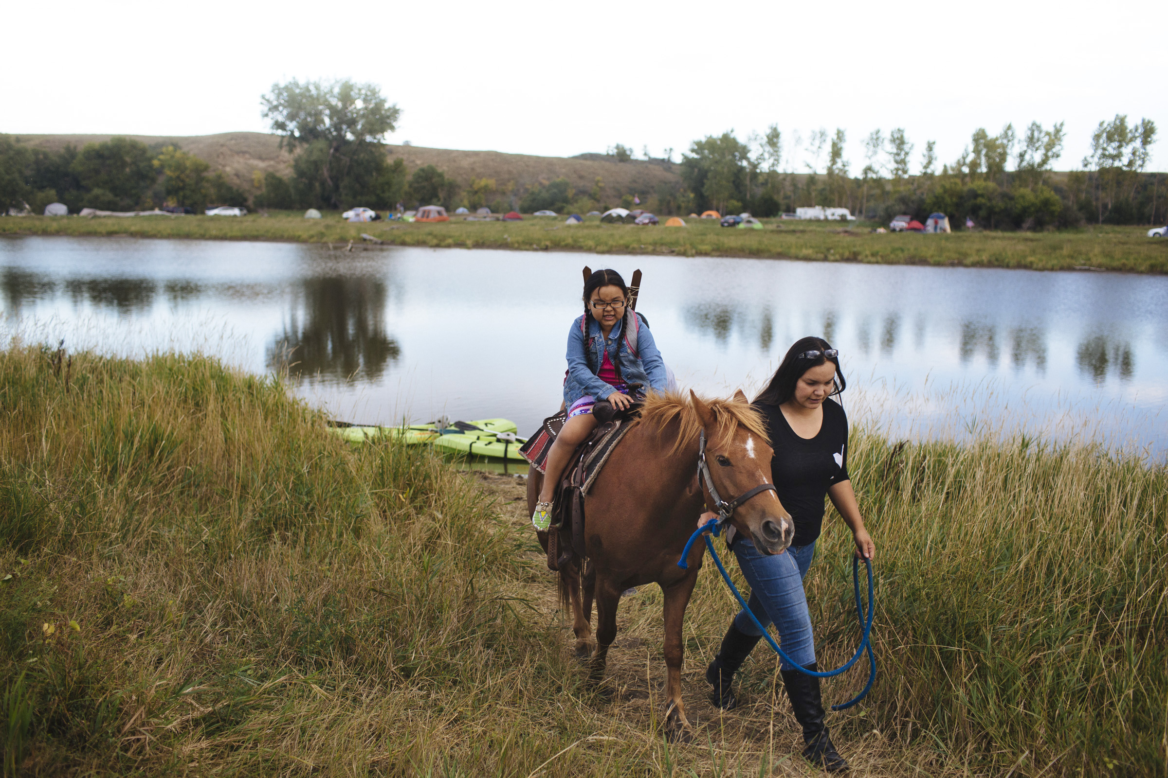 Marley Brown, 5, and her mother Tiffany Baker, 32, of Standing Rock Reservation take their horse, Pony Boy, for a walk along the Cannonball River in the Oceti Sakowin Camp on the outskirts of the Standing Rock Reservation on Thursday, Sept. 8, 2016. Thousands of people, including Native Americans from over 280 tribes, have come to Standing Rock to protest the construction of the Dakota Access Pipeline, a 1,172-mile underground crude oil pipeline which is expected to transport the oil from the Bakken region to an oil tank farm in Patoka, Illinois. (Photo by Angus Mordant/Groundtruth)