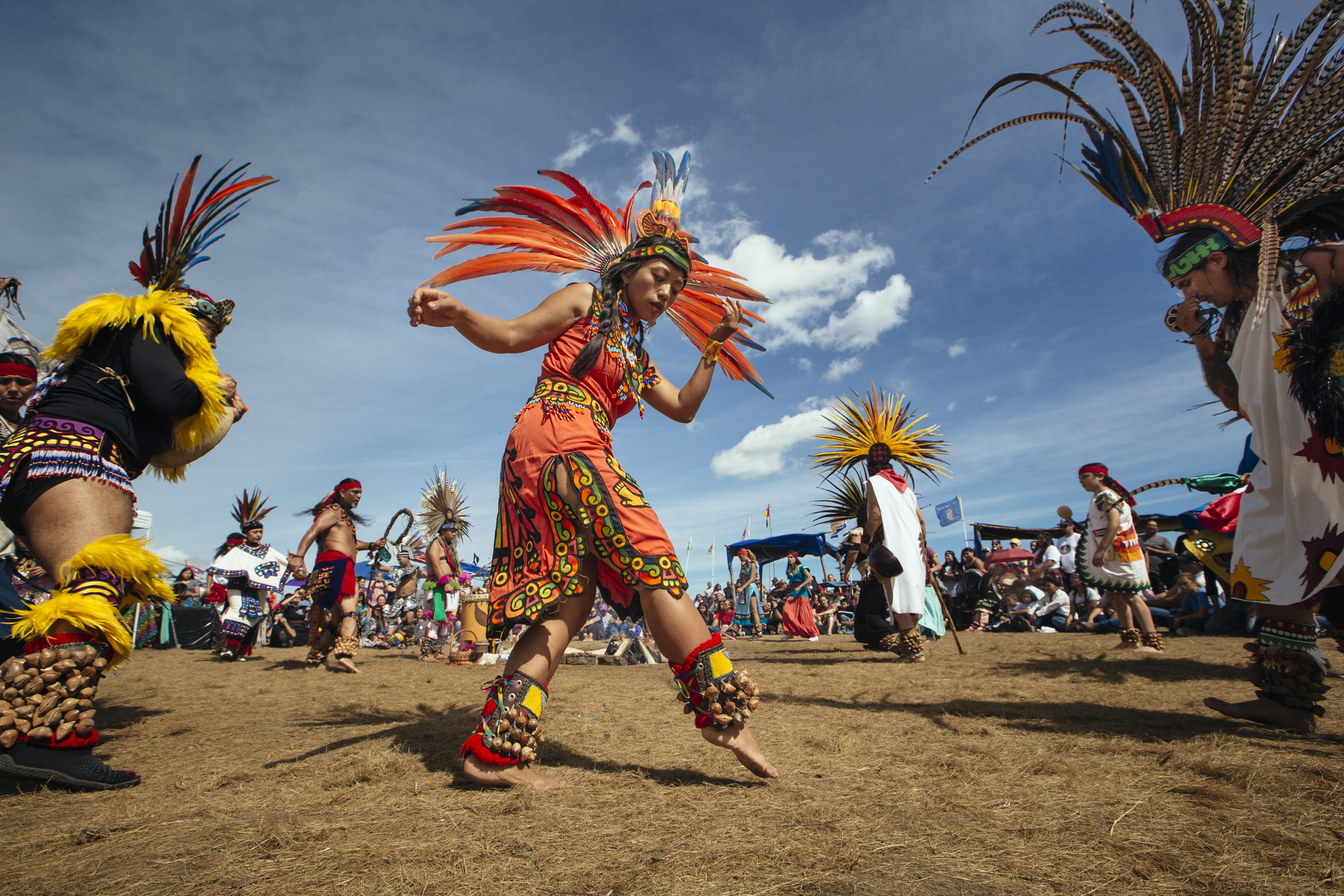 A group of dancers from various indigenous backgrounds perform a Mexicoto dance around the sacred fire at the Oceti Sakowin camp on Saturday, Sept. 10, 2016. Thousands of people, including Native Americans from over 280 tribes, have come to Standing Rock to protest the construction of the Dakota Access Pipeline, a 1,172-mile underground crude oil pipeline which is expected to transport crude oil from the Bakken region to an oil tank farm in Patoka, Illinois. (Photo by Angus Mordant/Groundtruth)