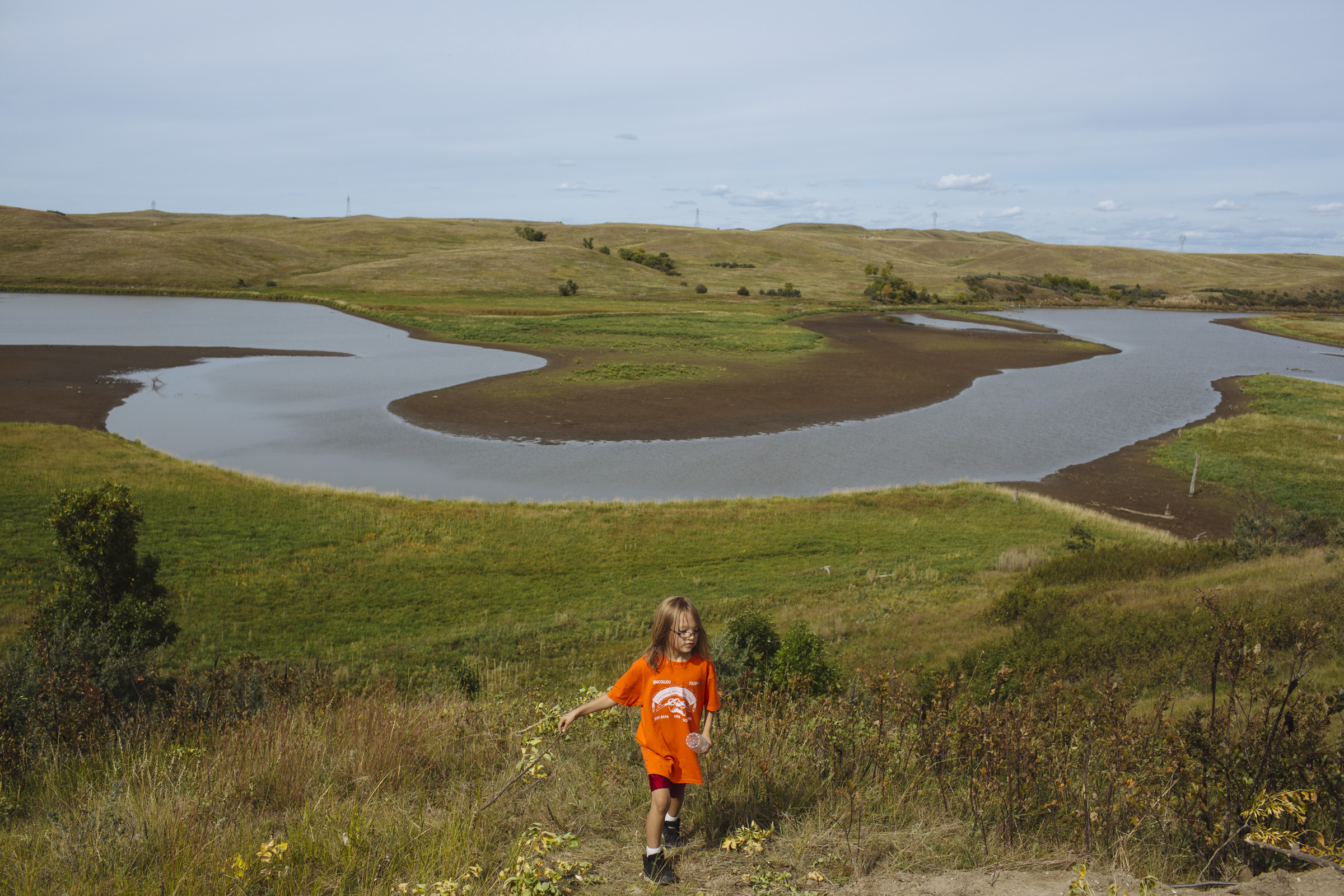 Royrie Scott, 7, of the Lakota Sioux Tribe plays on a hill overlooking a tributary which runs in to the Missouri River on Saturday, Sept. 10, 2016. The electrical poles on the horizon mark an existing utility corridor, which the Dakota Access Pipeline will follow through the region. (Photo by Angus Mordant/GroundTruth)