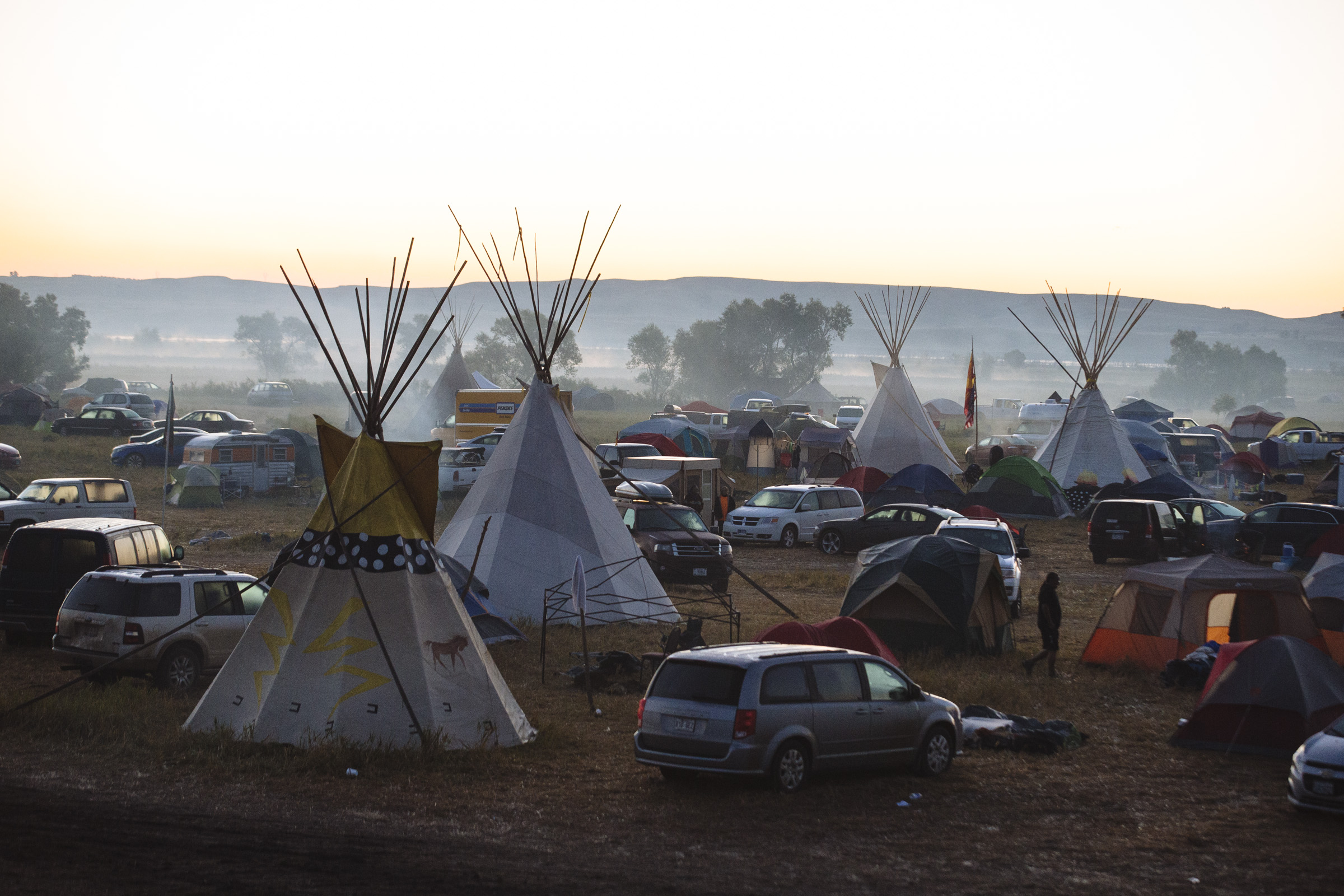 A light fog is seen on the Cannon Ball River as the sun rises over the Oceti Sakowin Camp on the outskirts of the Standing Rock Reservation on Saturday, Sept. 10, 2016. Native Americans from over 280 tribes have gathered to protest the construction of the Dakota Access Pipeline through the Missouri River and over sacred burial sites. (Photo by Angus Mordant/Groundtruth)