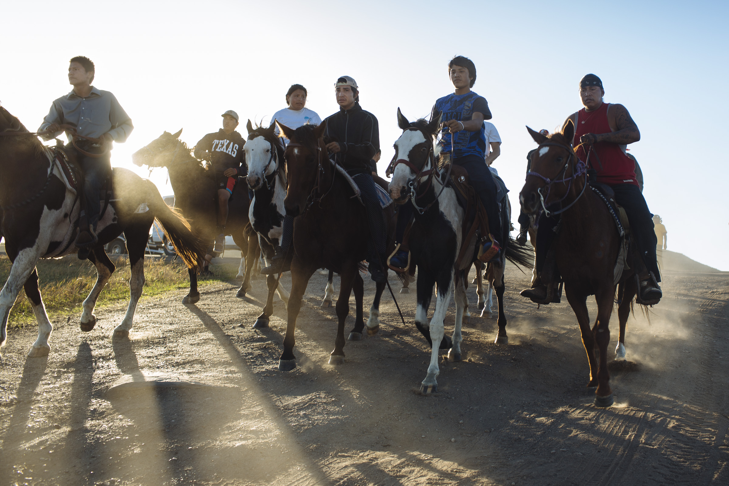 A group of Native American men on horseback enter the Oceti Sakowin Camp ahead of a group of youth, who ran approximately 300 miles from the Pine Ridge Reservation to join the protest movement at Standing Rock on Saturday, Oct. 1, 2016. Thousands of people, including Native Americans from over 280 tribes, have come to Standing Rock to protest the construction of the Dakota Access Pipeline, a 1,172-mile underground crude oil pipeline which is expected to transport crude oil from the Bakken region to an oil tank farm in Patoka, Illinois. (Photo by Angus Mordant/Groundtruth)