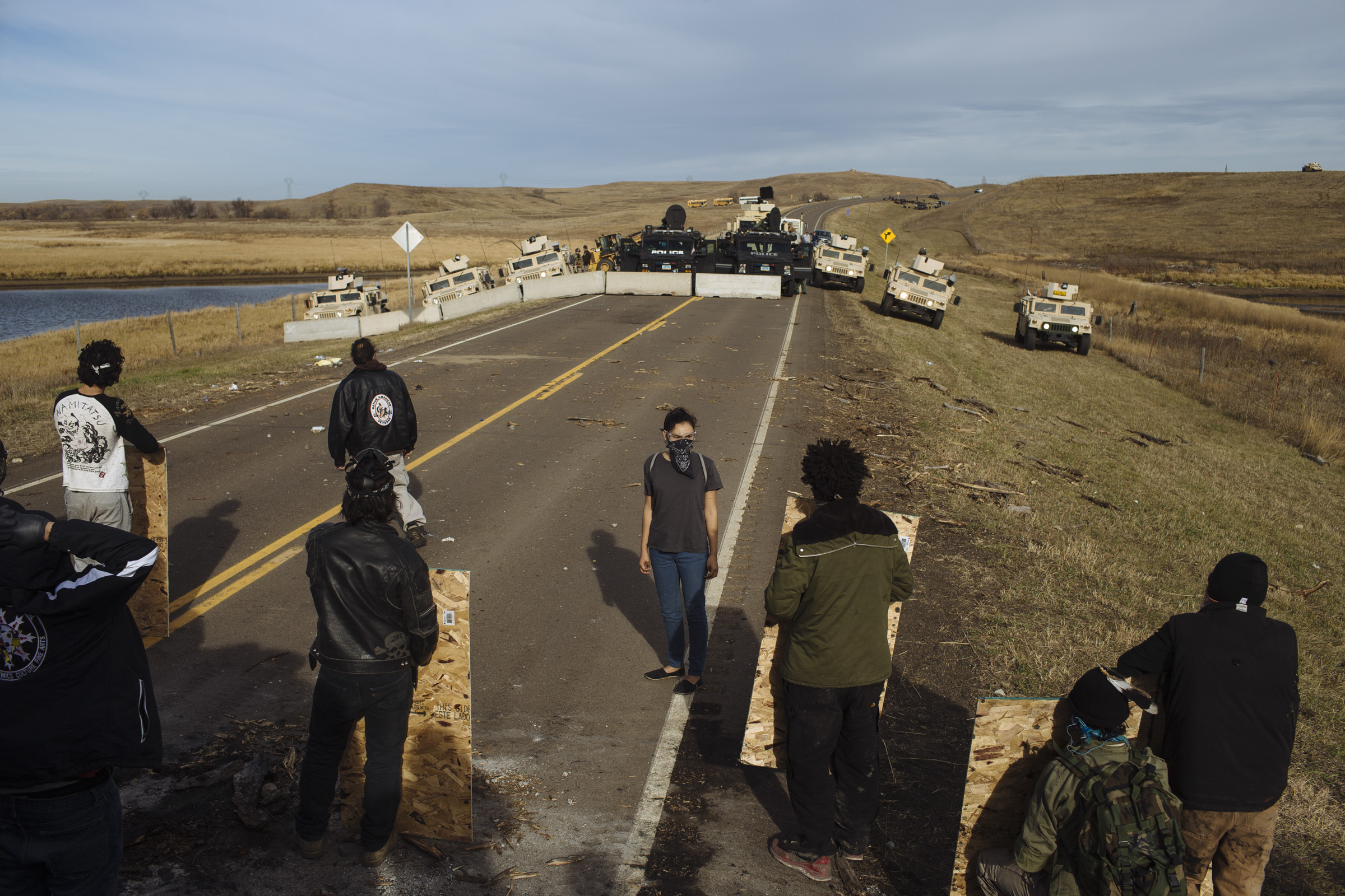 A small group of protesters face off against police as a road block is constructed by the Backwater Bridge on Highway 1806, just a day after police cleared the northernmost protest encampment on Thursday, Oct. 27, 2016. The roadblock on Backwater Bridge has become a key point of conflict as protestors state it blocks access for emergency responders. Police argue that the bridge is unsafe and that it's essential to separate protestors from pipeline security and construction workers. (Photo by Angus Mordant/Groundtruth)