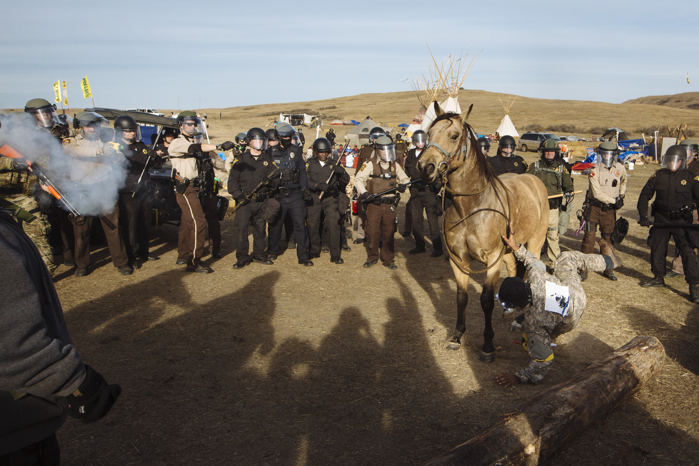 "Smokey White, 18, is shot with a sponge grenade and tazed off his horse as riot police move through a camp set up by protestors in the path of the Dakota Access Pipeline near Standing Rock, North Dakota, on Thursday, Oct. 27, 2016. ""This is modern war,"" said Smokey. ""The only difference is we don't have assault riffles – our weapon is our prayer."" (Photo by Angus Mordant/GroundTruth)"