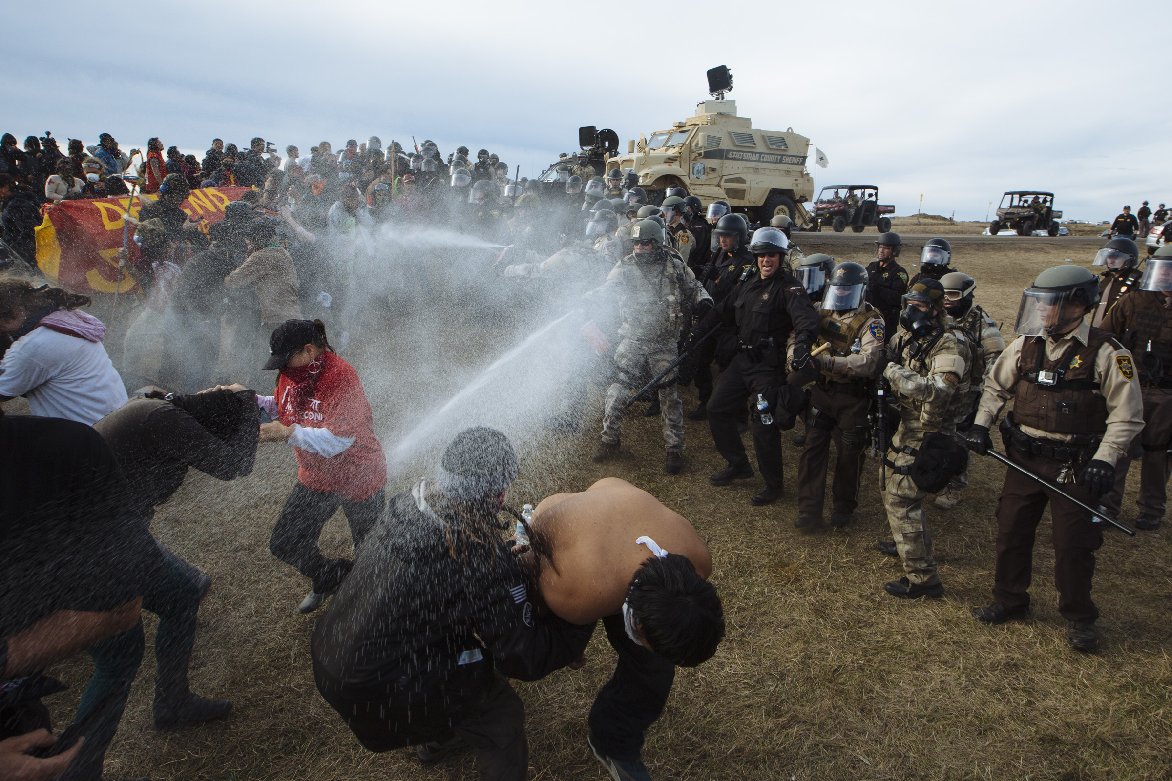 Riot police use pepper spray on a mostly Native American group of peaceful protesters near the Standing Rock Reservation in North Dakota on Thursday, Oct. 27, 2016. Police moved in to clear protestors out of a camp set up directly in the path of the Dakota Access Pipeline. (Photo by Angus Mordant/GroundTruth)