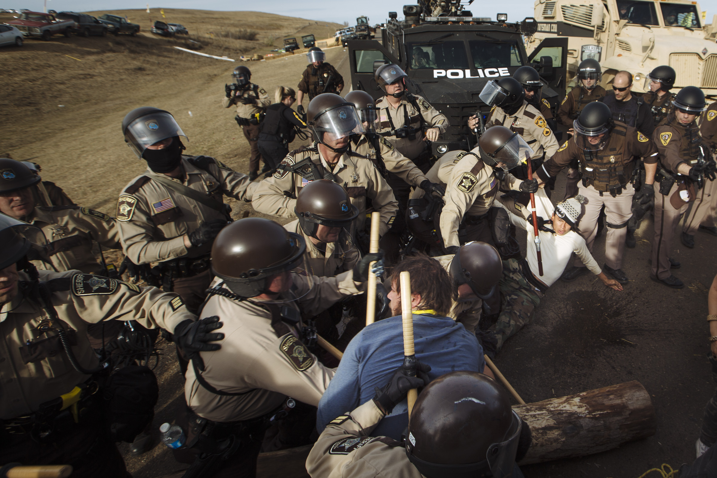 Riot police conduct mass arrests as they clear the northernmost protest encampment, which was built directly in the path of the Dakota Access Pipeline. Thursday, Oct. 27, 2016. (Photo by Angus Mordant/GroundTruth)