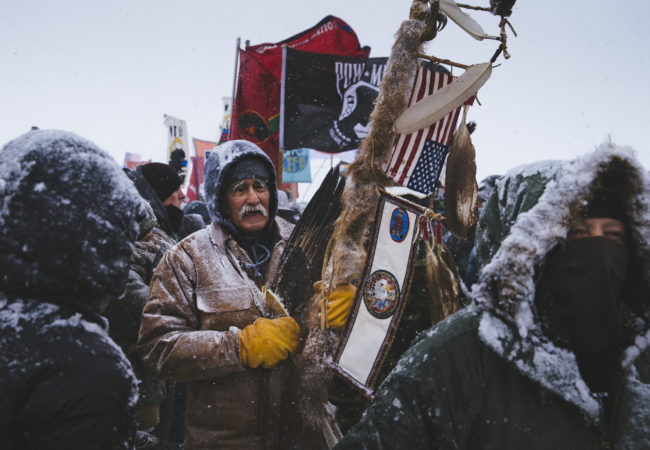 Glenn Scott, 60, a member of the Chippewa tribe and a Vietnam veteran, participates in a march of over 2,000 veterans from the Oceti Sakowin Camp to the police road block on Backwater Bridge on Monday, Dec. 5, 2016. Thousands of veterans deployed to Standing Rock to support the protest movement, offering to act as a human shield against police force. (Photo by Angus Mordant/GroundTruth)