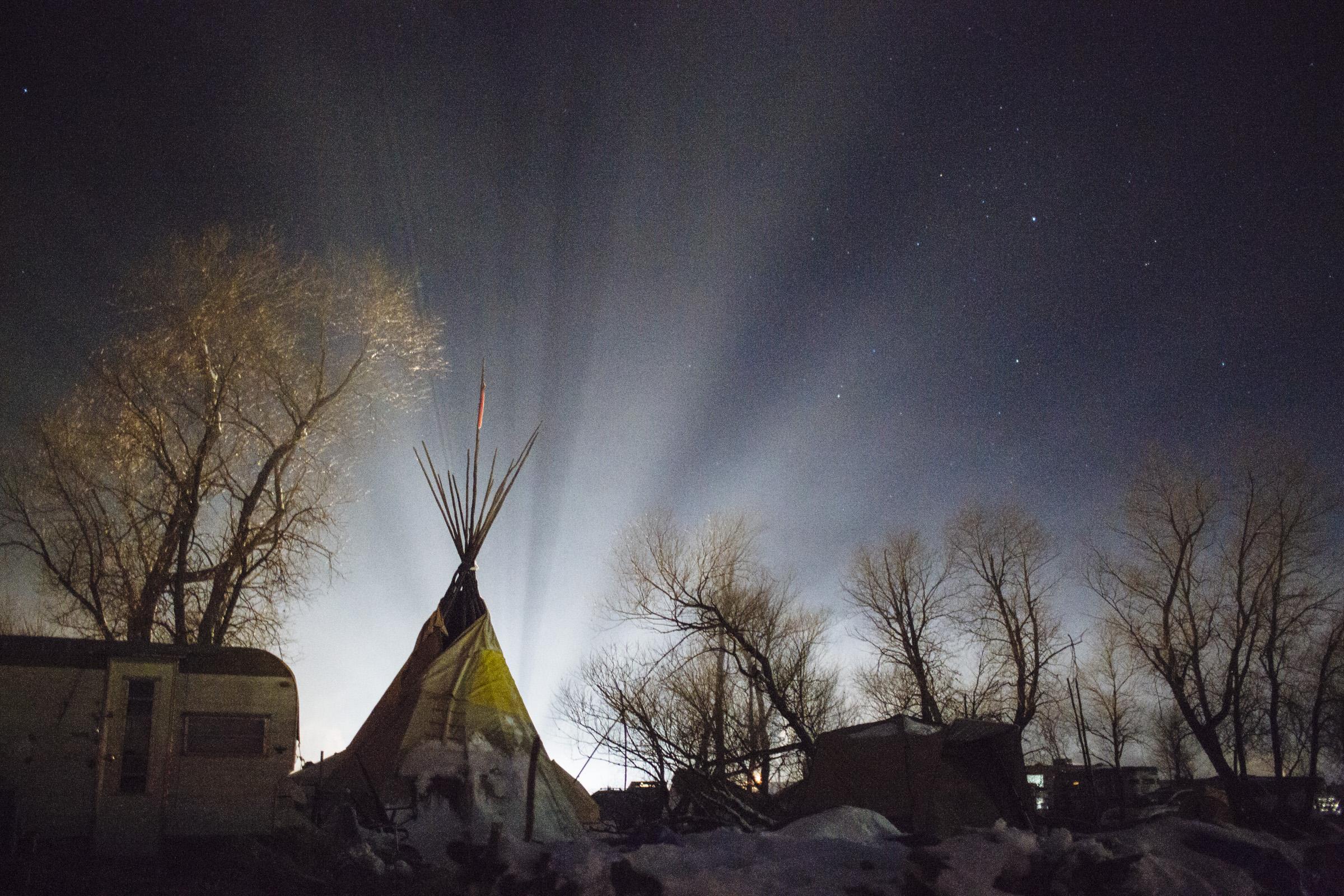 Car headlights illuminate fog surrounding a tepee at the Oceti Sakowin Camp near Cannon Ball, North Dakota on Sunday, Dec. 4, 2016. (Photo by Angus Mordant/GroundTruth)