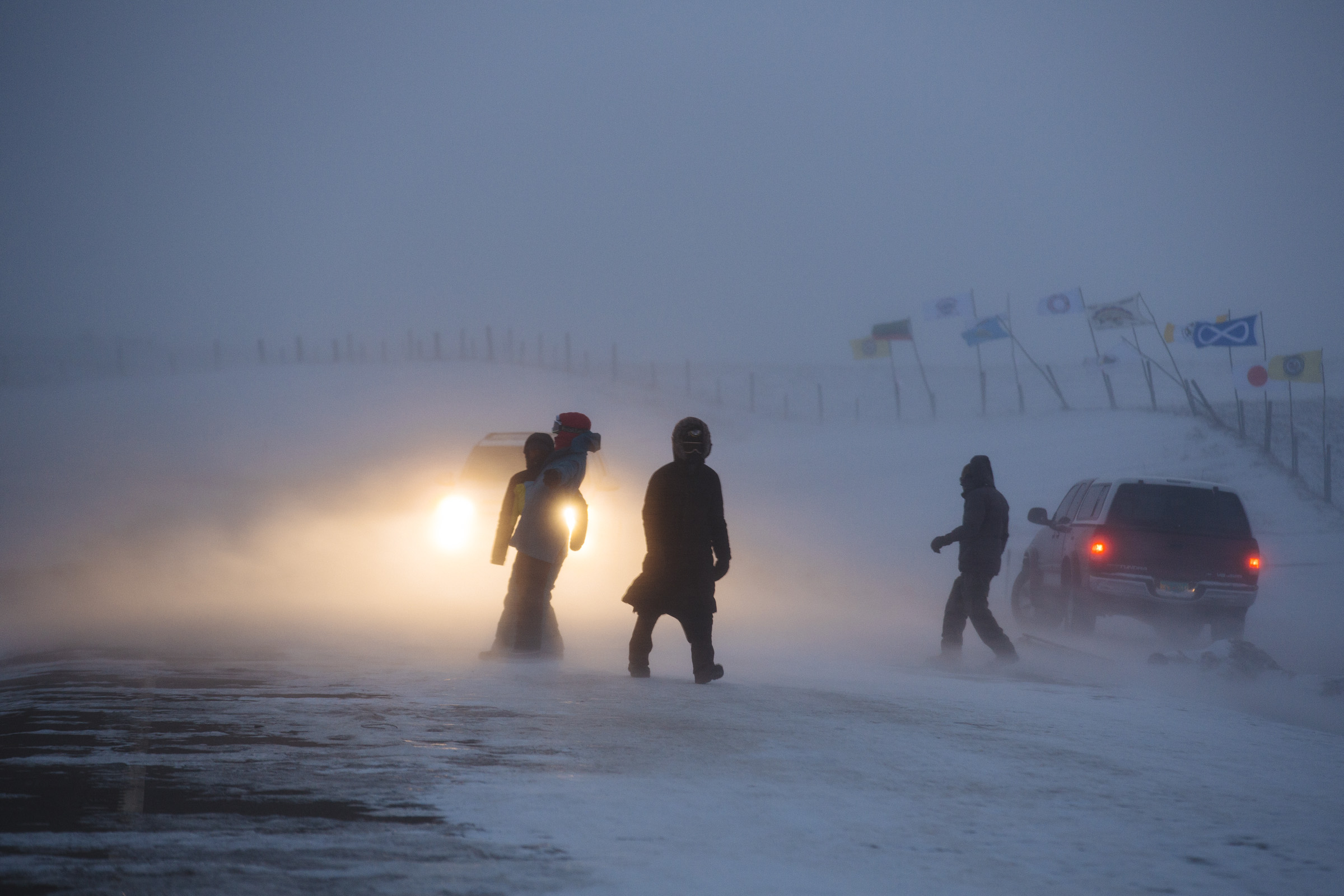 People struggle to walk during a snowstorm on Highway 1806, outside the Oceti Sakowin Camp on Wednesday, Dec. 7, 2016. (Photo by Angus Mordant/GroundTruth)