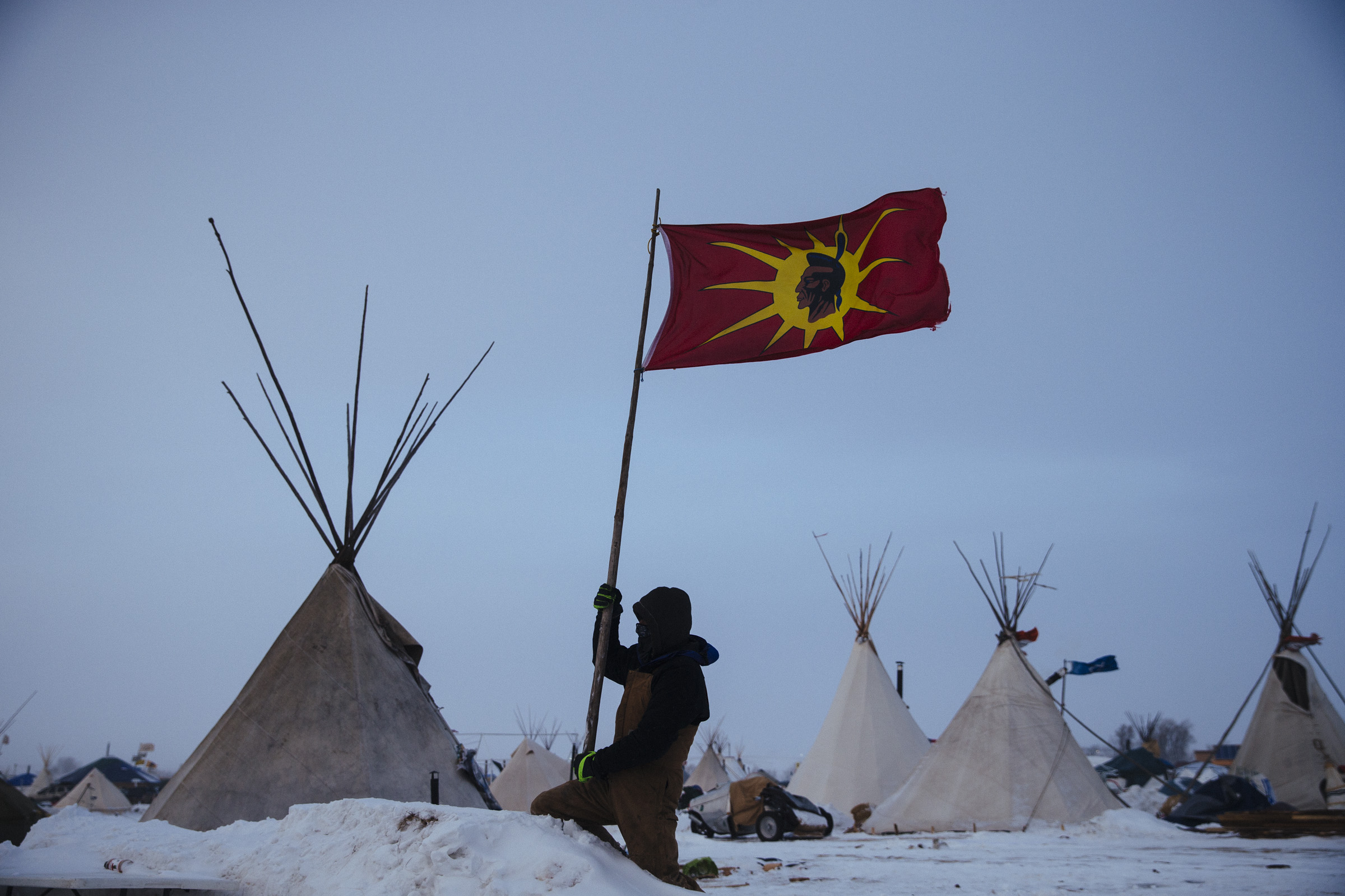 A protester removes a flag from his campsite before leaving the Oceti Sakowin Camp on Wednesday, Dec. 7, 2016. Thousands left the protest camp after blizzard conditions swept through it.(Photo by Angus Mordant/GroundTruth)