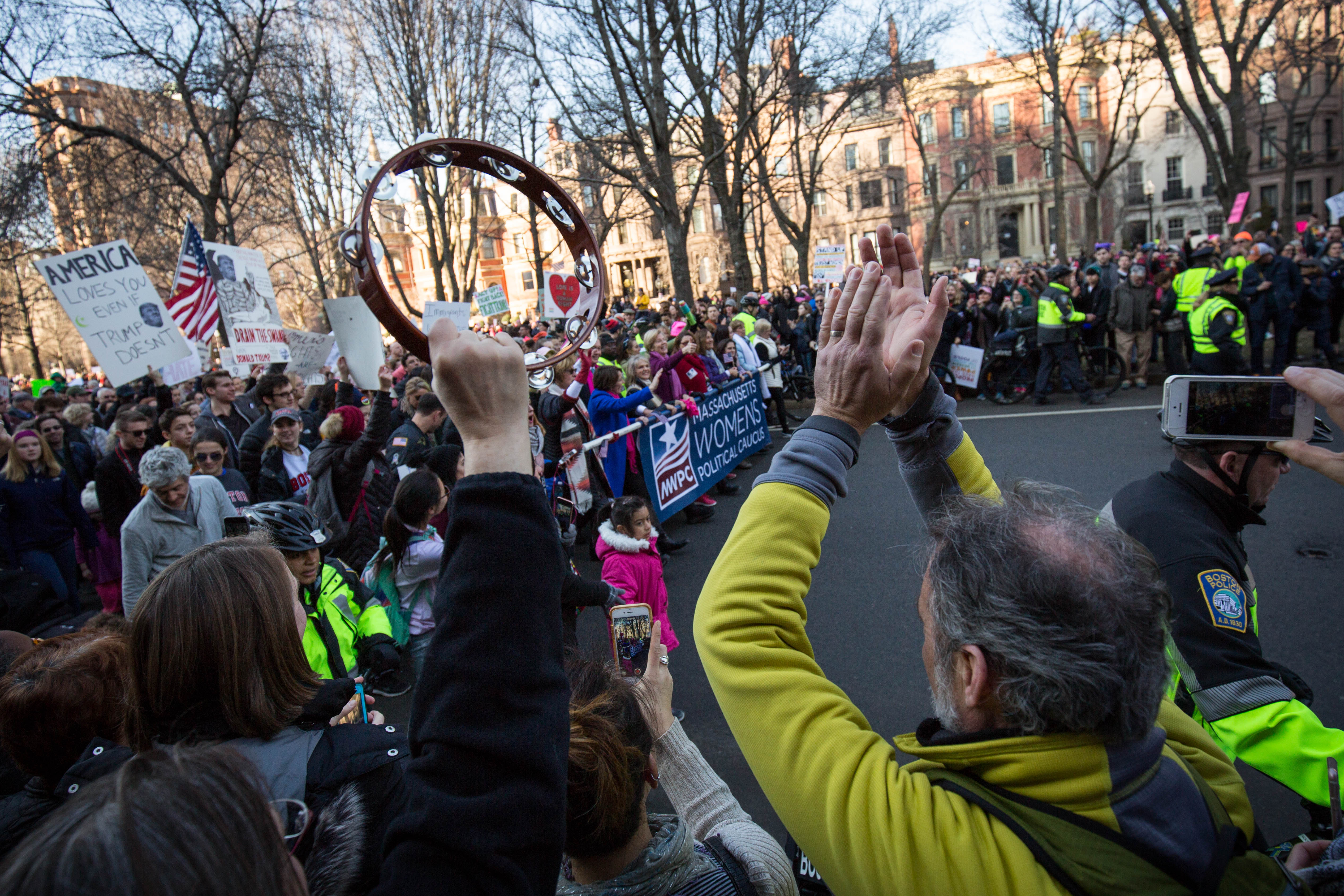 Protesters play the tambourine as a band comes through the city of Boston on Jan. 21, 2017. (Photo by Alastair Pike)