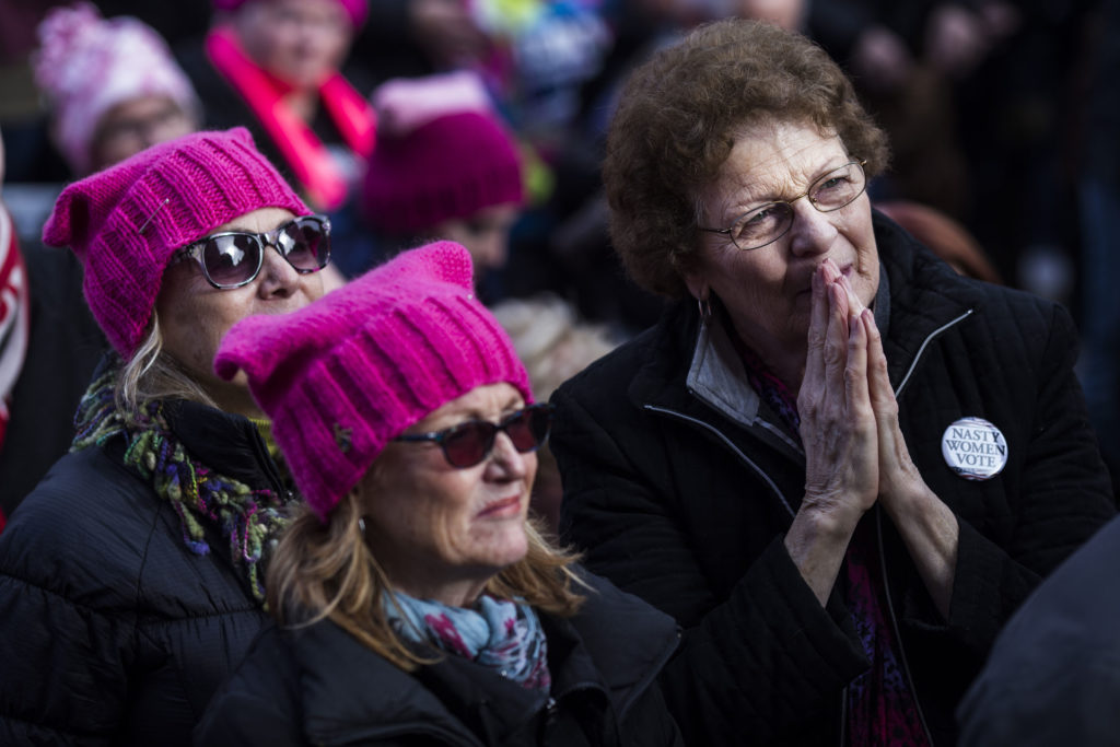 Mille Wrench, 72, of Kalamazoo, Mich., listens to speakers during the Women's March on Lansing outside of the Michigan State Capitol Building in Lansing, Mich., on Saturday, January 21, 2017. (Photo by Brittany Greeson/GroundTruth)
