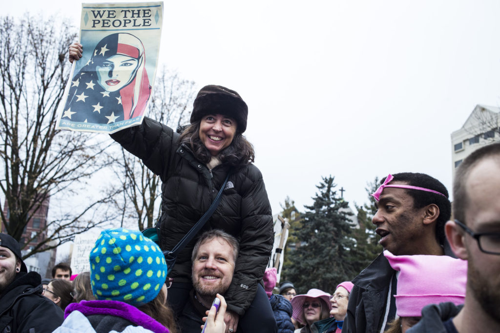 Monica Silva, 49, of East Lansing, Mich., sits on her husband's shoulders during the Women's March on Lansing outside of the Michigan State Capitol Building in Lansing, Mich., on Saturday, January 21, 2017. (Photo by Brittany Greeson/GroundTruth)