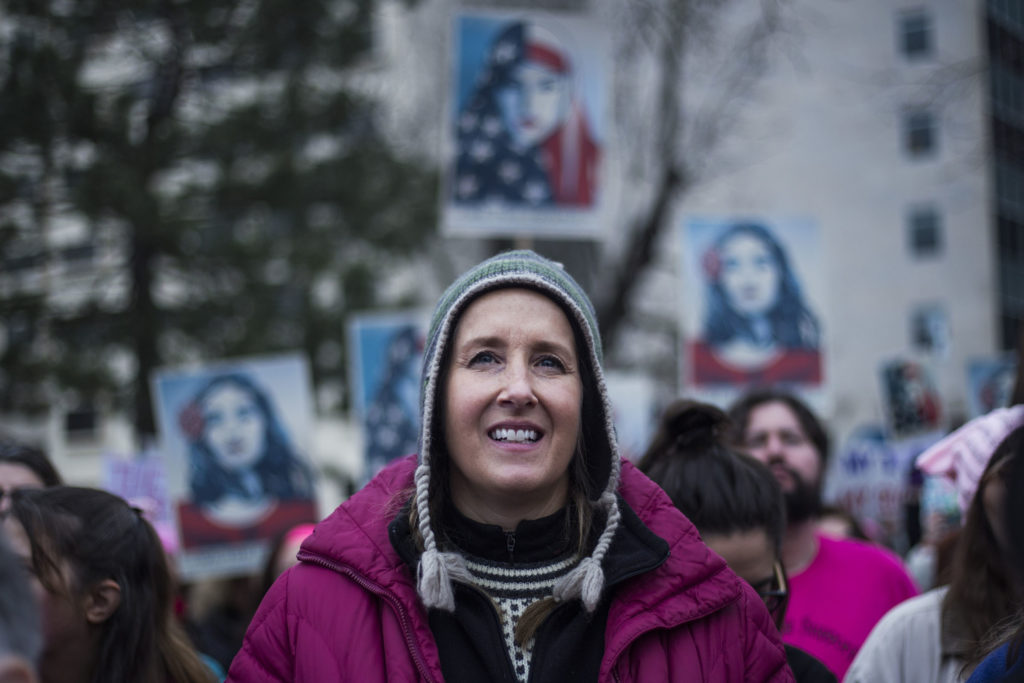 "Jennifer Day, 49, of Ann Arbor, listens to speakers for the Women's March on Lansing outside of the Michigan State Capitol Building in Lansing, Mich., on Saturday, January 21, 2017. ""I'm definitely feeling inspired. I want to put a voice to what kind of change we want to see,"" Day said. (Photo by Brittany Greeson/GroundTruth)"