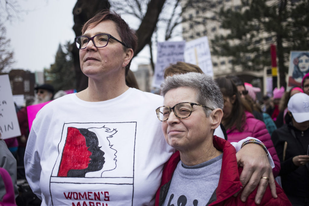 "Lisa Mapp, 54, and marital partner, Chris Smith, 44, of Mason, Mich., embrace while listening to speakers during the Women's March on Lansing outside of the Michigan State Capitol Building in Lansing, Mich., on Saturday, January 21, 2017. The pair said they came to the march in hopes of taking power back, rather than feeling powerless. ""It's really wonderful seeing this many people,"" Smith said. (Photo by Brittany Greeson/GroundTruth)"