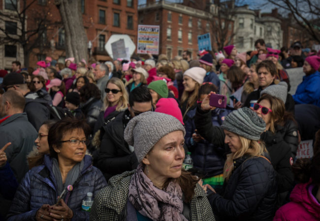 """A woman sheds a tear as the song, """"America the Beautiful: Together We Stand"""" plays in the Boston Common during the Boston Women's March on Jan. 21, 2017. (Photo by Alastair J. Pike/GroundTruth)"""
