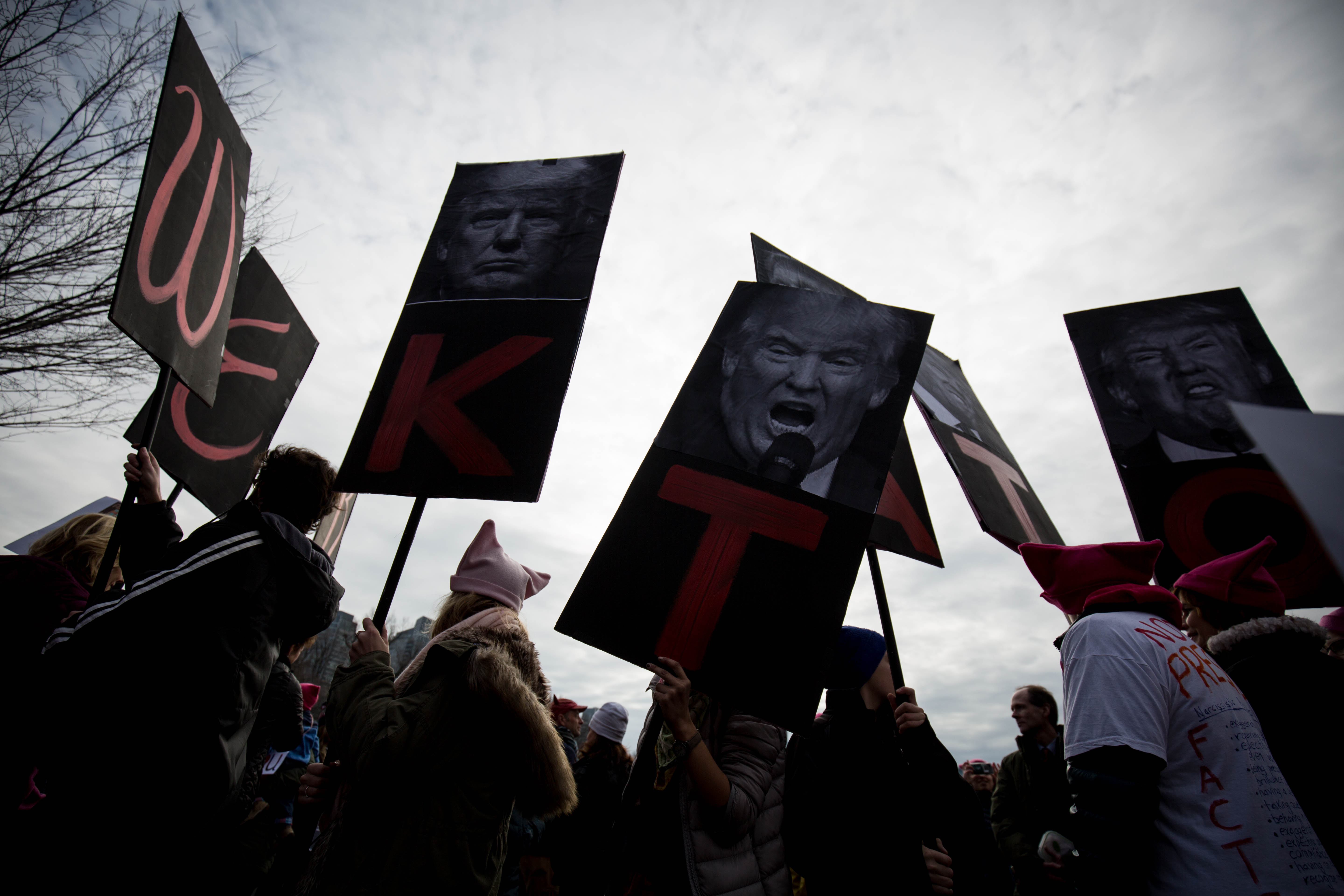 """Protestors hold up collective signs calling President Donald J. Trump a """"dicktator"""" in the Boston Commons on Jan. 21, 2017. (Photo by Alastair Pike)"""