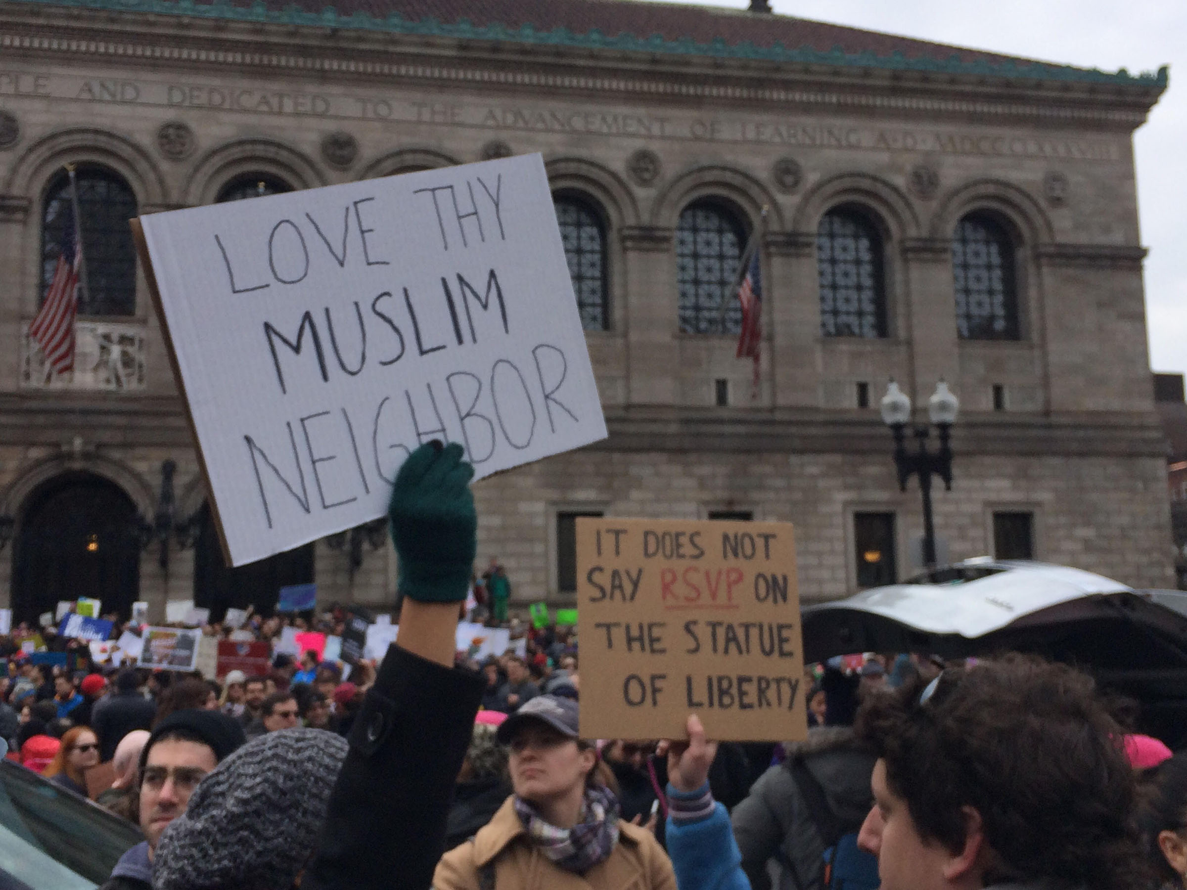 """Signs read """"Love thy Muslim neighbor"""" and """"It does not say RSVP on the Statue of Liberty"""" at a demonstration in Boston's Copley Square on January 29, 2017. (Photo by Giulia Afiune/GroundTruth)"""