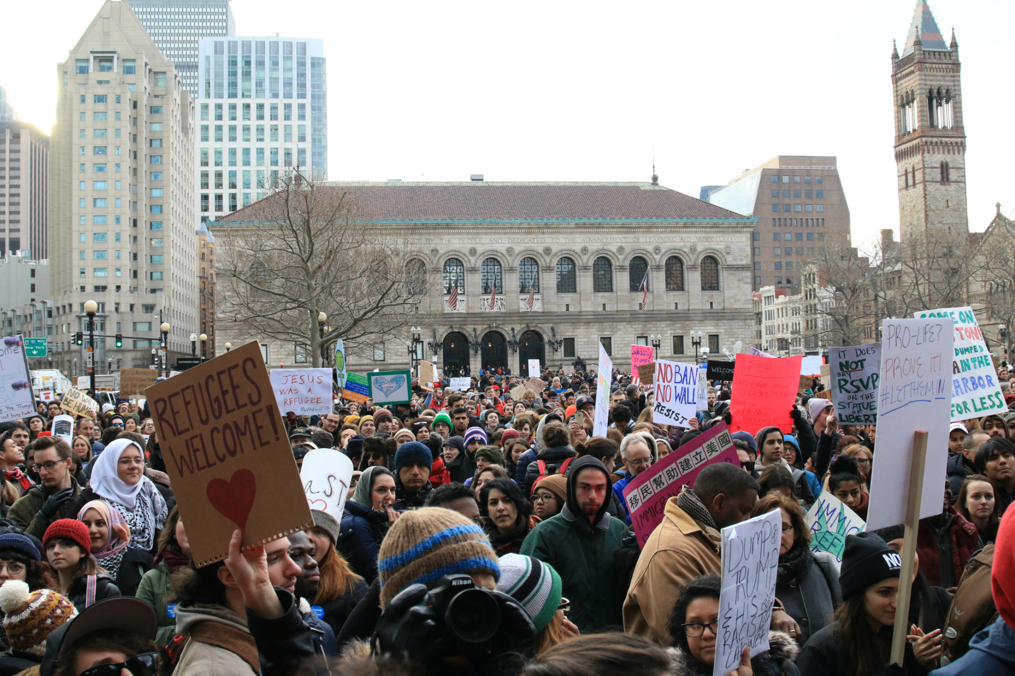 """A crowd gathers in protest against President Donald Trump's immigration ban, in front of the Boston Public Library on Jan. 29, 2017. Signs read """"Refugees welcome"""" and """"Jesus was a refugee."""" (Photo by Giulia Afiune/GroundTruth)"""