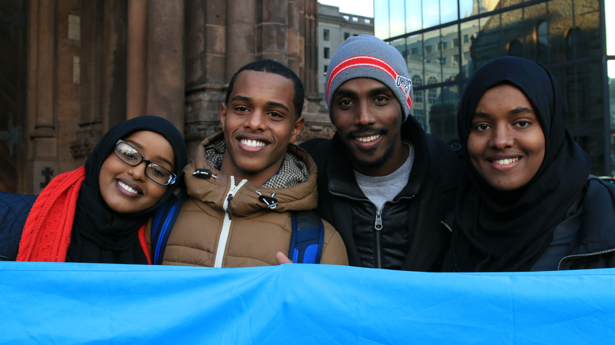 """Hibo Moallim (left) was born in Kenya, but her family is originally from Somalia, one of the seven majority-Muslim countries affected by Trump's ban. During a protest in Boston's Copley Square, she and her cousins led the crowd singing """"This is what the democracy looks like,"""" and other chants. """"This ban goes against everything America stands for,"""" she said. (Photo by Giulia Afiune/GroundTruth)"""
