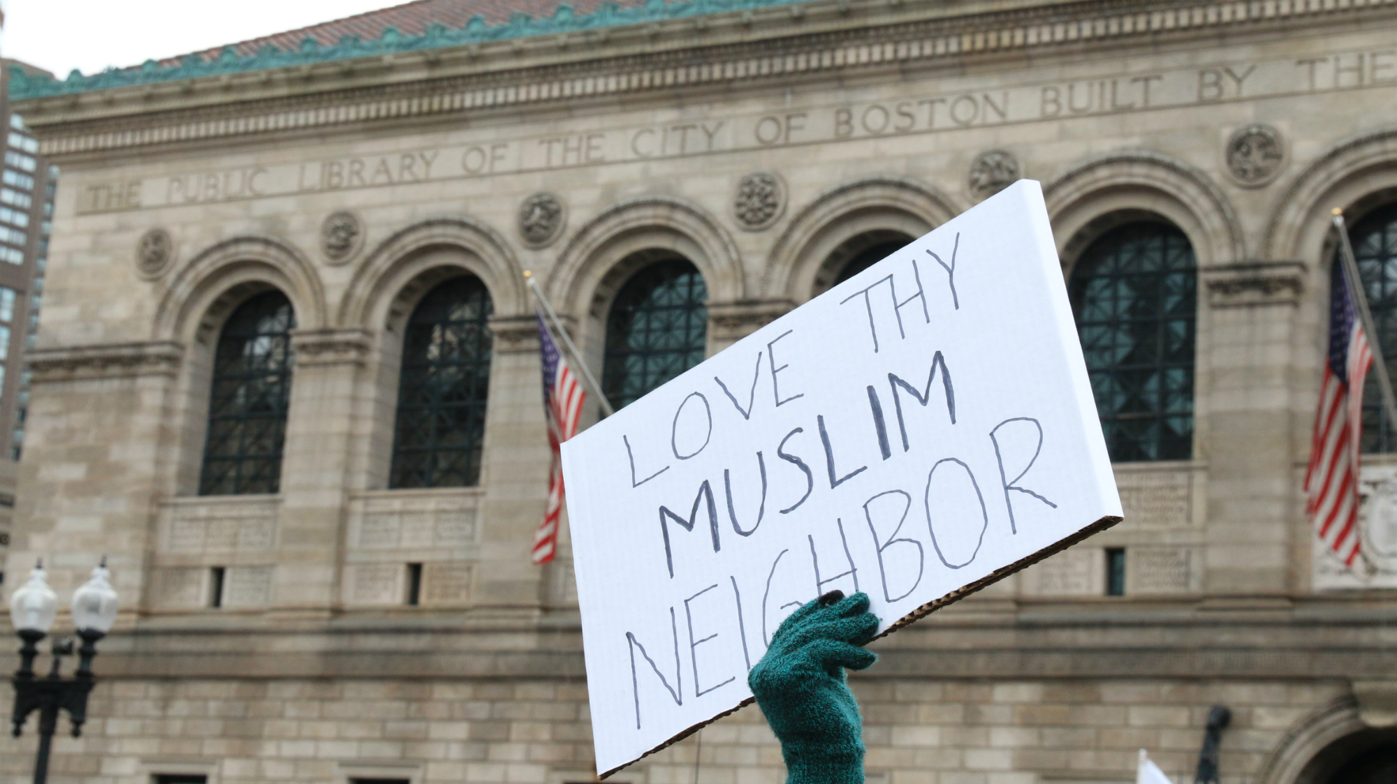 """A sign reads """"Love thy Muslim neighbor"""" at the protest in Boston's Copley Square against President Donald Trump's executive order on immigration. (Photo by Giulia Afiune/GroundTruth)"""