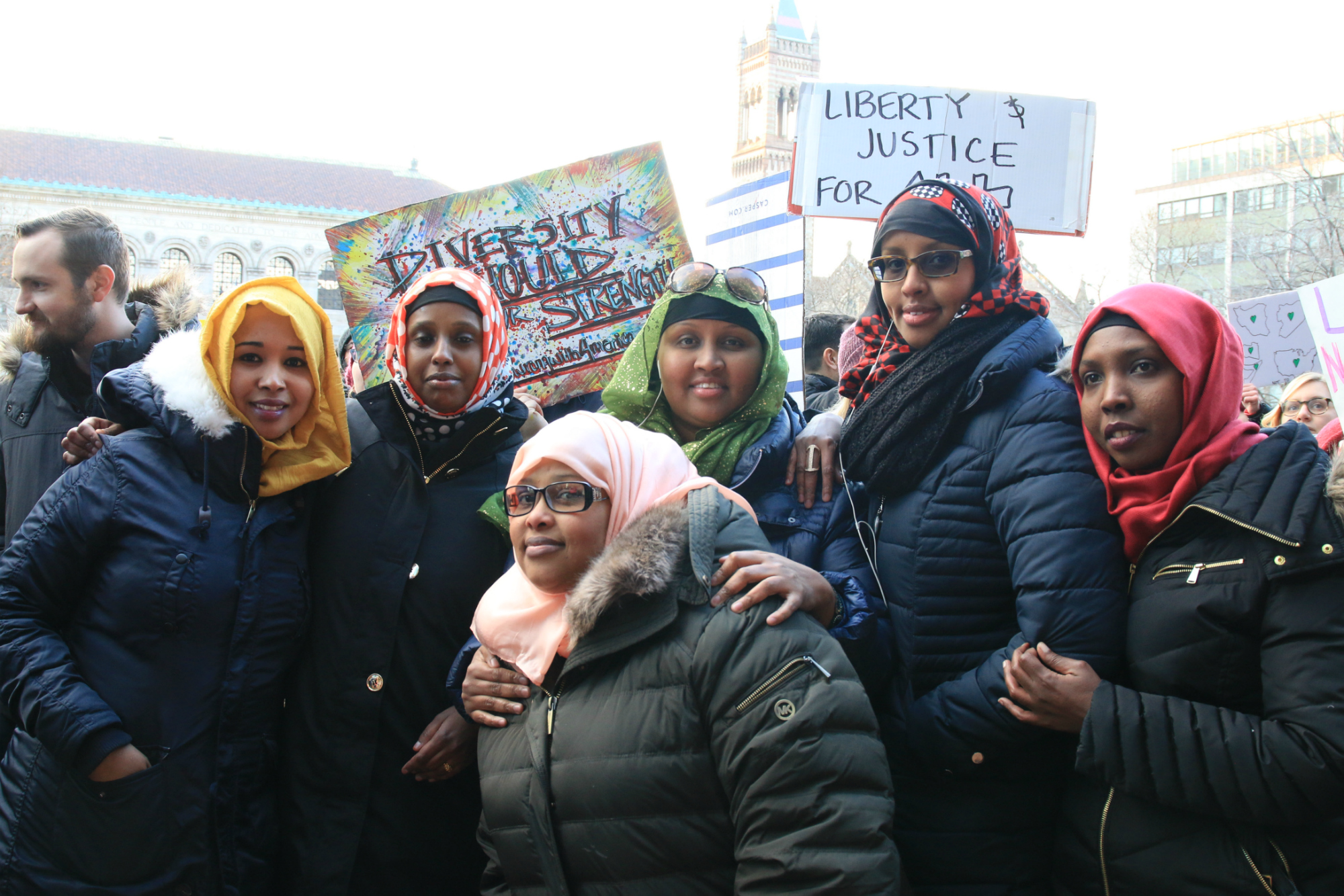"""Somali-immigrant Rukia Tahlil (center) has been living in the United States for 23 years. """"My country was going through a civil war at the time, so we came here for safety. But since Donald Trump was elected and citizens of America turned to hate, I don't feel safe here anymore,"""" she said. With her cousins and friends, she protested against President Donald Trump immigration ban against people from seven majority-Muslim countries, including her own. (Photo by Giulia Afiune/GroundTruth)"""