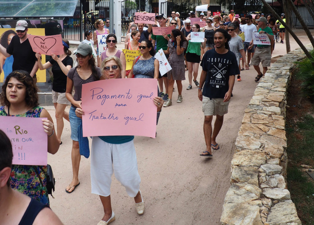 "Demonstrators take part in the Women's March on Rio. The sign in the foreground reads ""Equal pay for equal work."" (Photo by Catherine Osborn/GroundTruth)"
