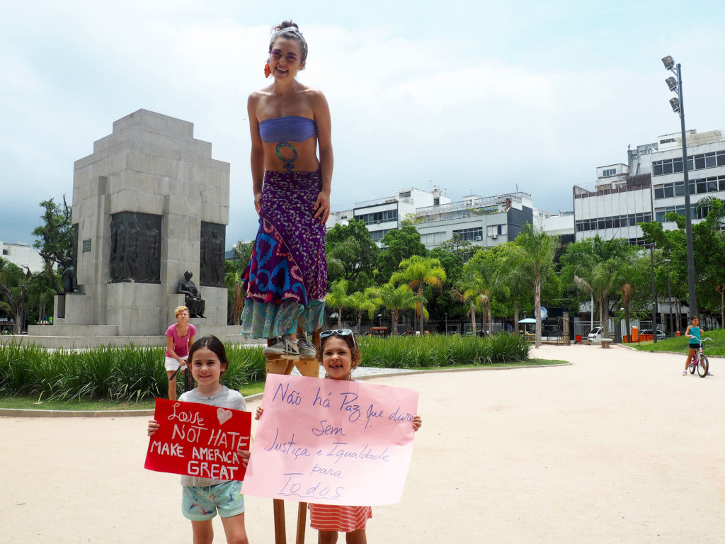 "A marcher on stilts and two children with their signs pose for a photo. The sign on the right reads, ""There is no peace that lasts without justice and equality for all."" (Photo by Catherine Osborn/GroundTruth)"
