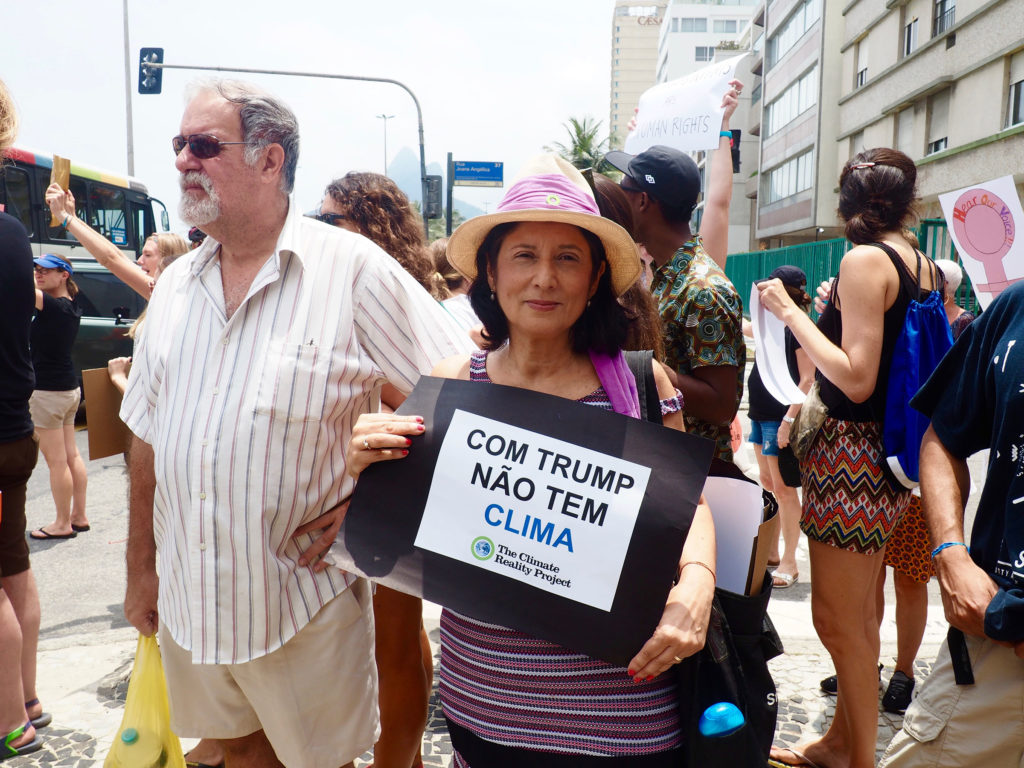 "A demonstrator in Rio holds a sign that says ""With Trump, there's no climate."" (Photo by Catherine Osborn/GroundTruth)"